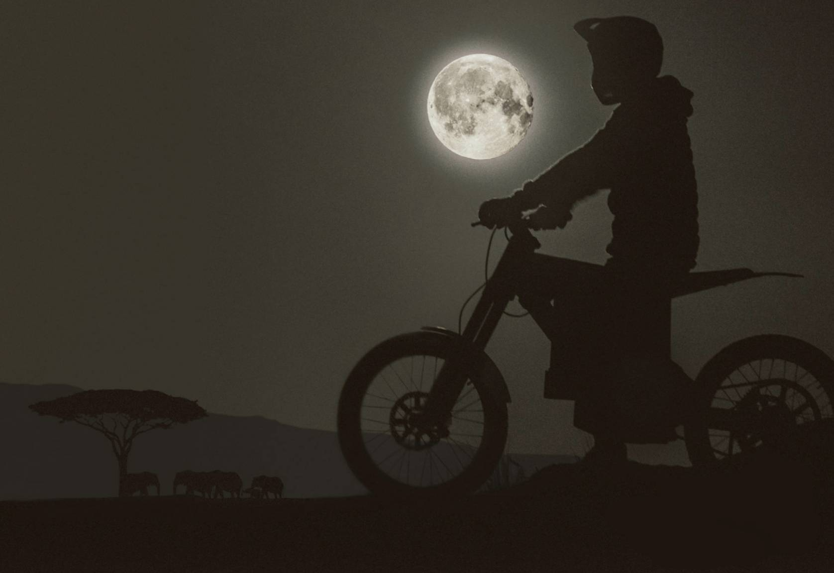 silhouette of rider in moto-helmet on a CAKE electric bush bike