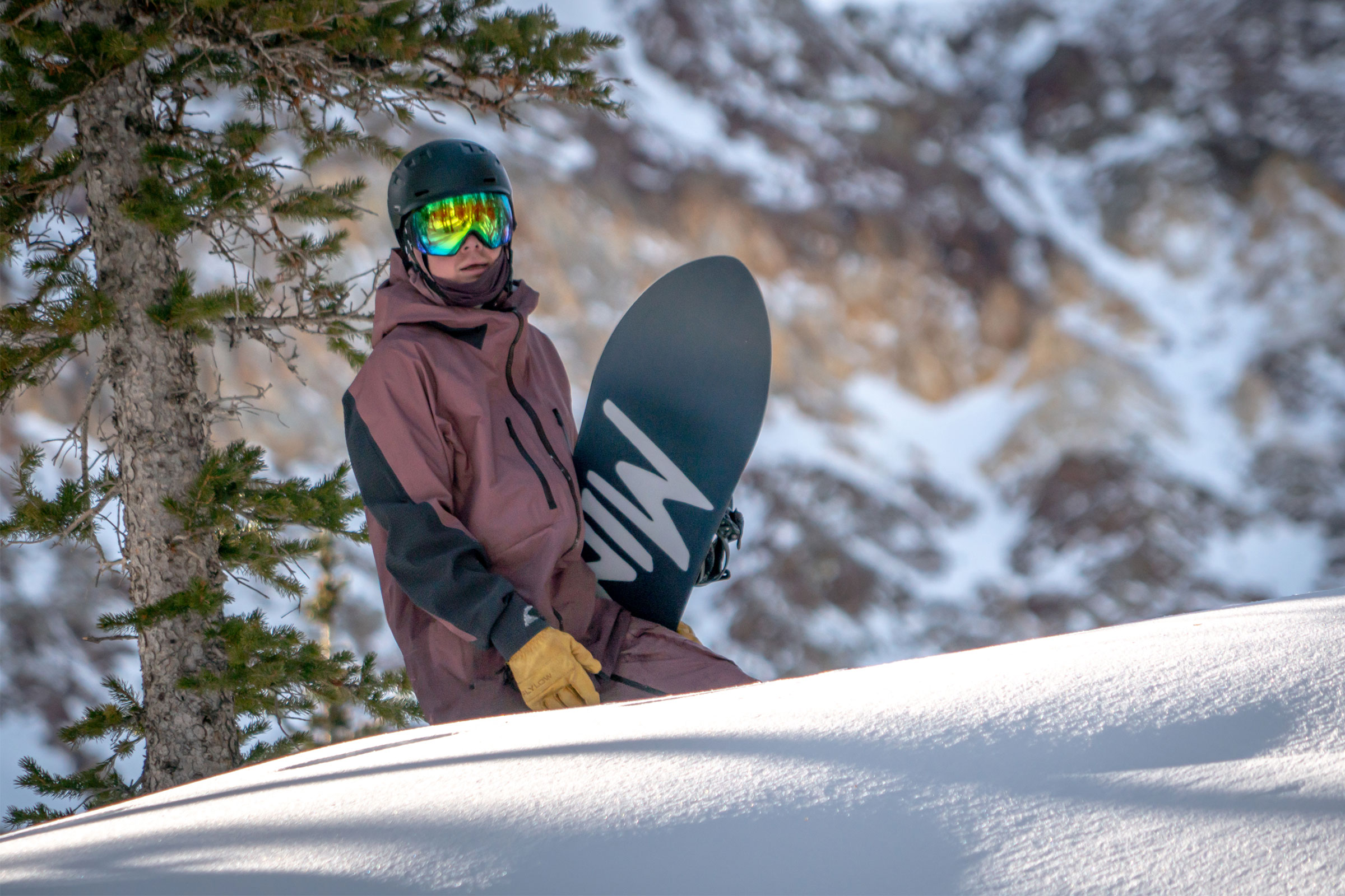 Rider wearing Burton's Mine 77 kit and mittens carrying snowboard uphill