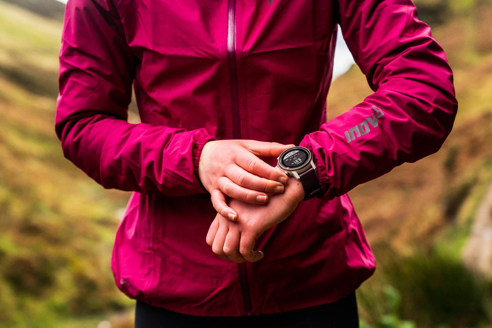 runner wearing magenta inov-8 jacket and COROS watch