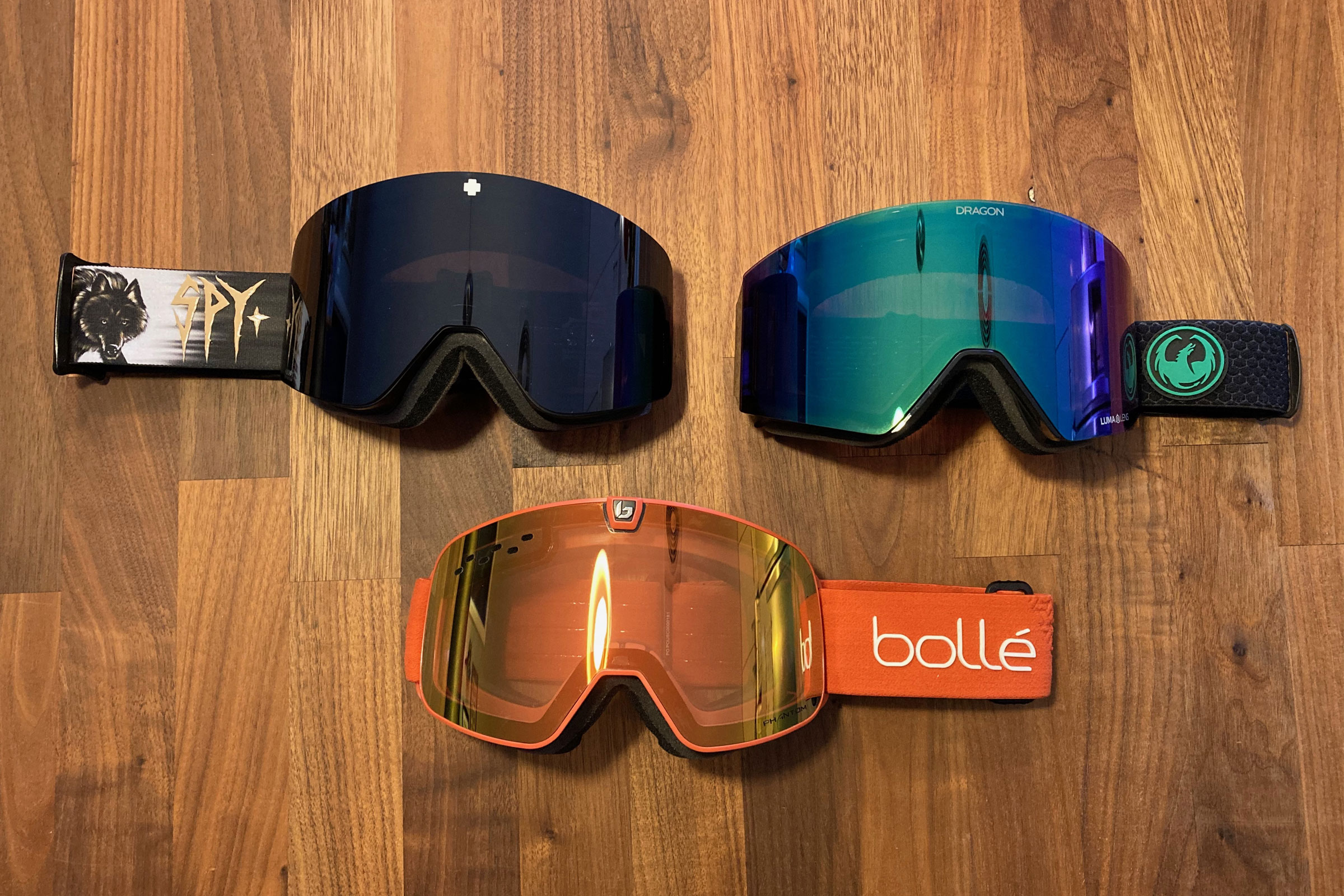 3 quick change lens goggles from 3 different brands on wood table