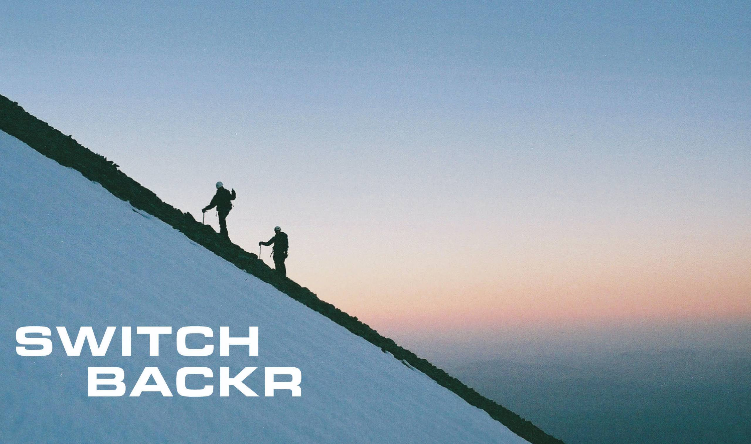 two hikers on a steep slope at sunset, with switchbackr logo in white text