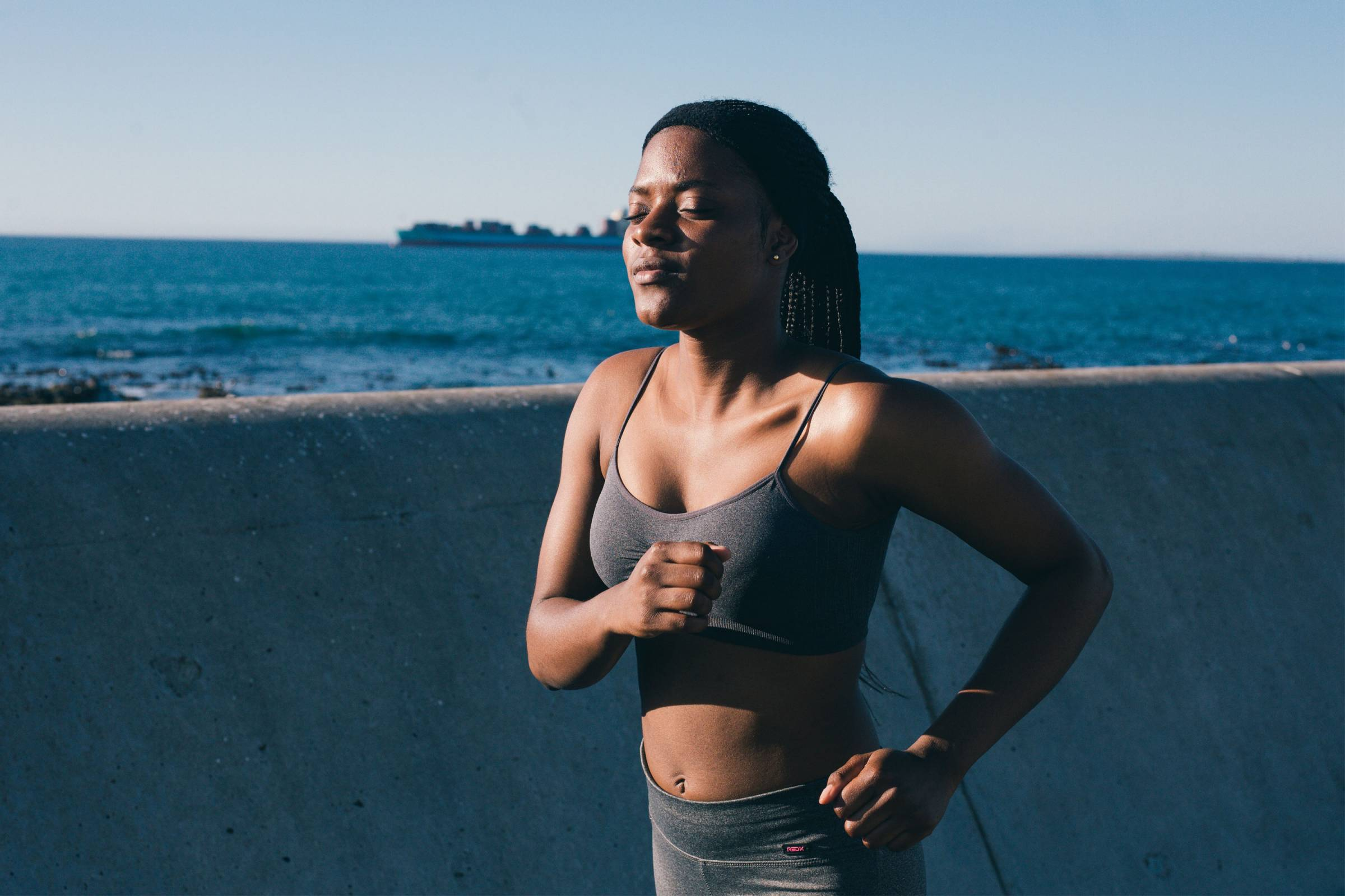 Black woman running with eyes closed along coast in sports bra and tights
