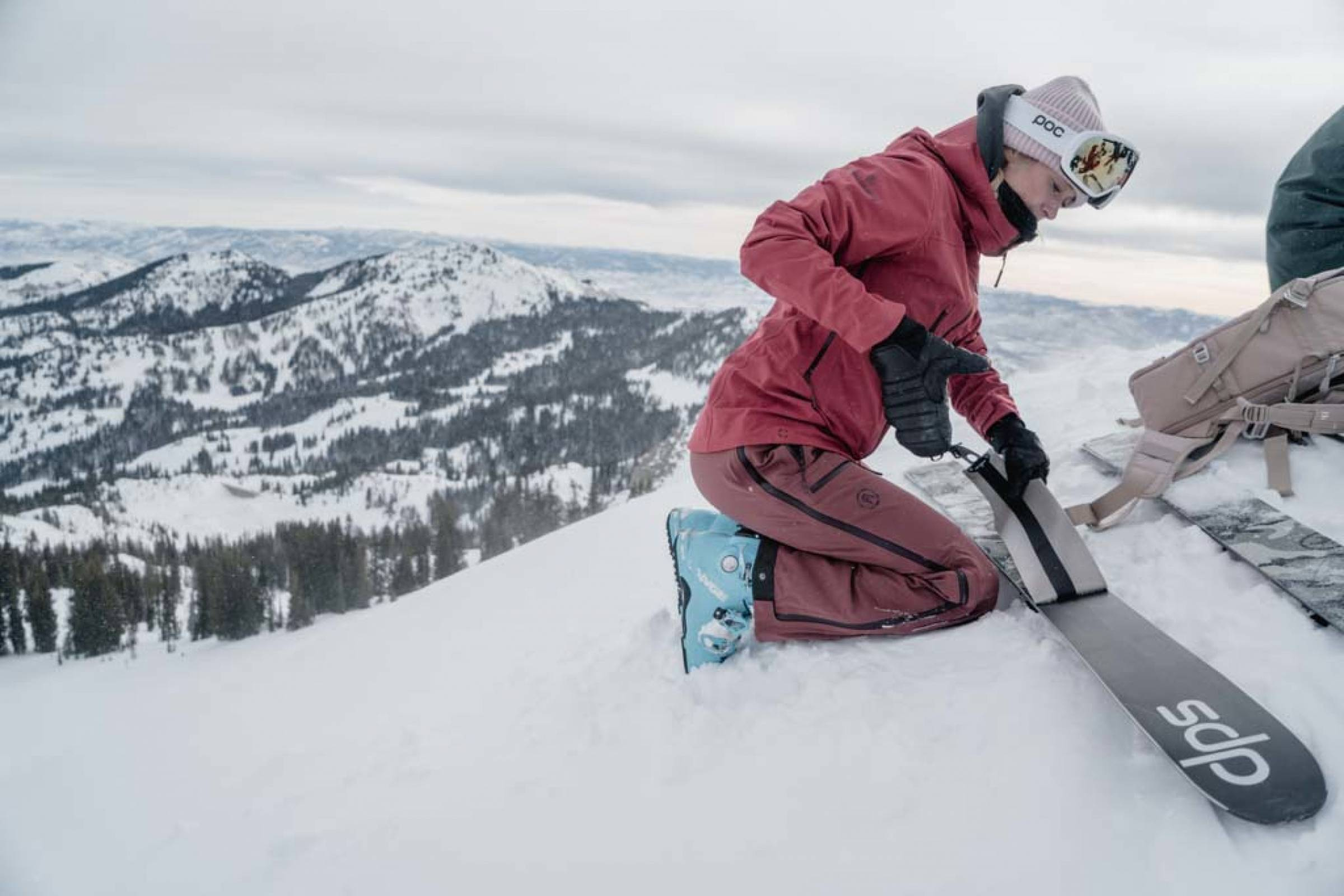 Backcountry Skier Removing Skins in Mountains
