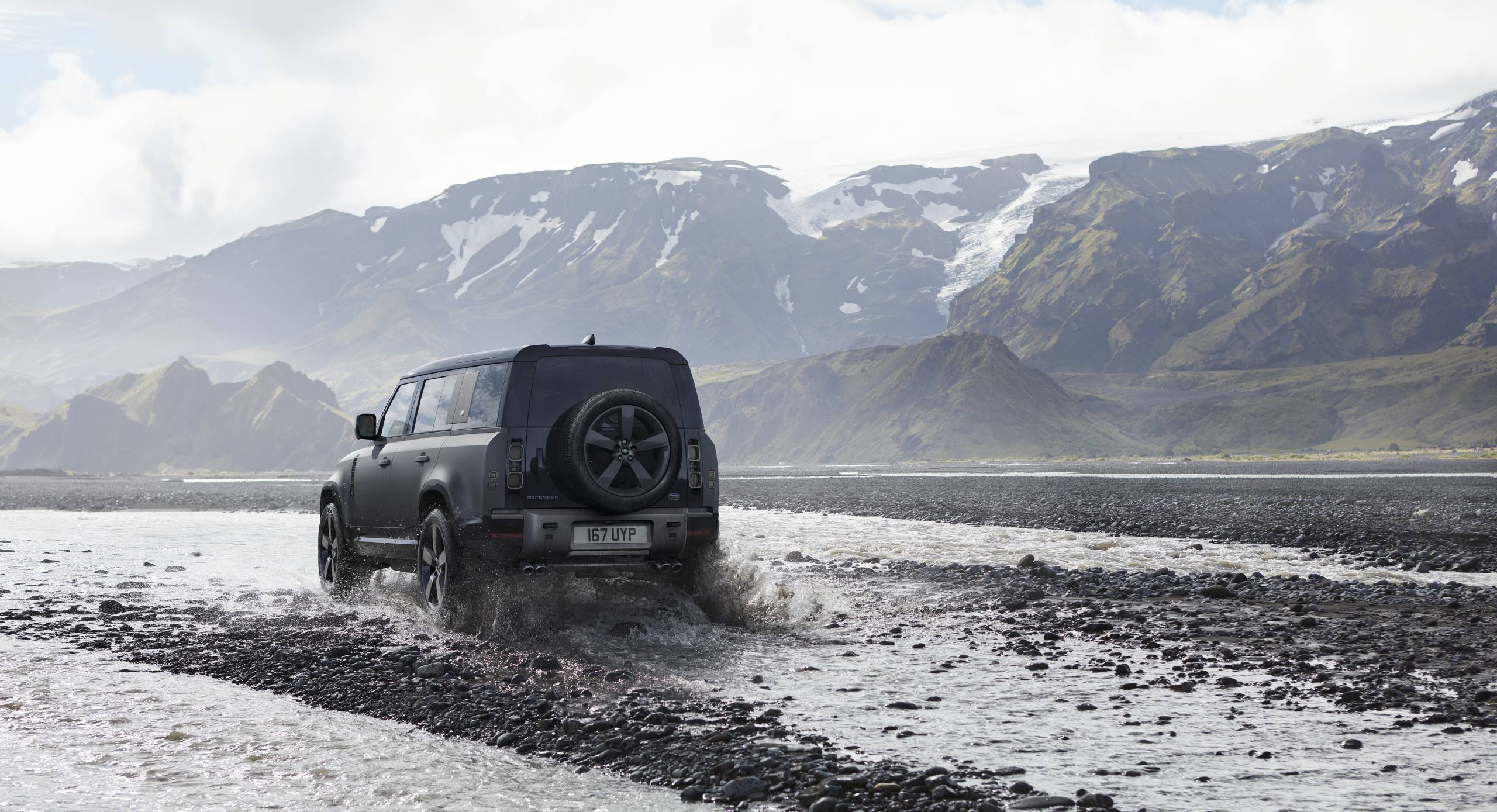 2022 Land Rover Defender 110 V8 Carpathian Edition driving up a river in mountains