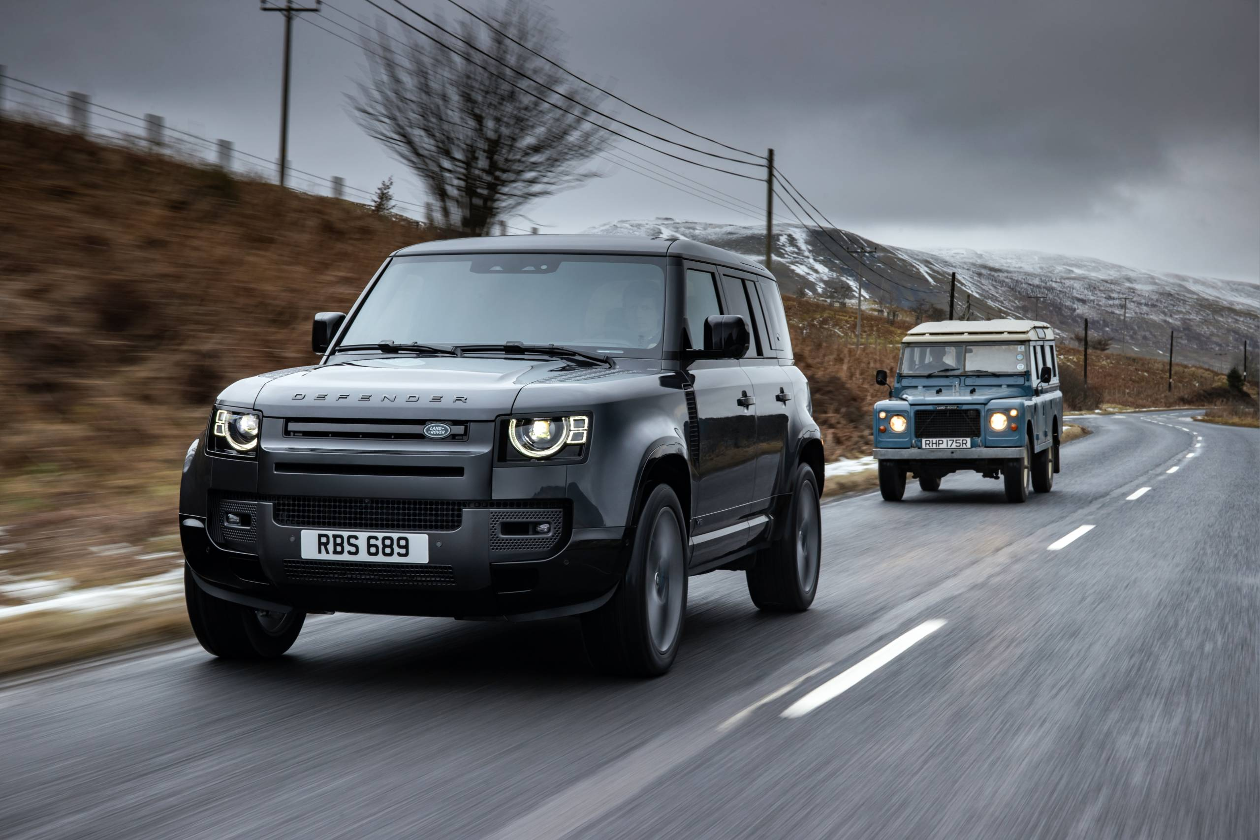 2022 Land Rover Defender 110 V8 on road with old Series Rover following