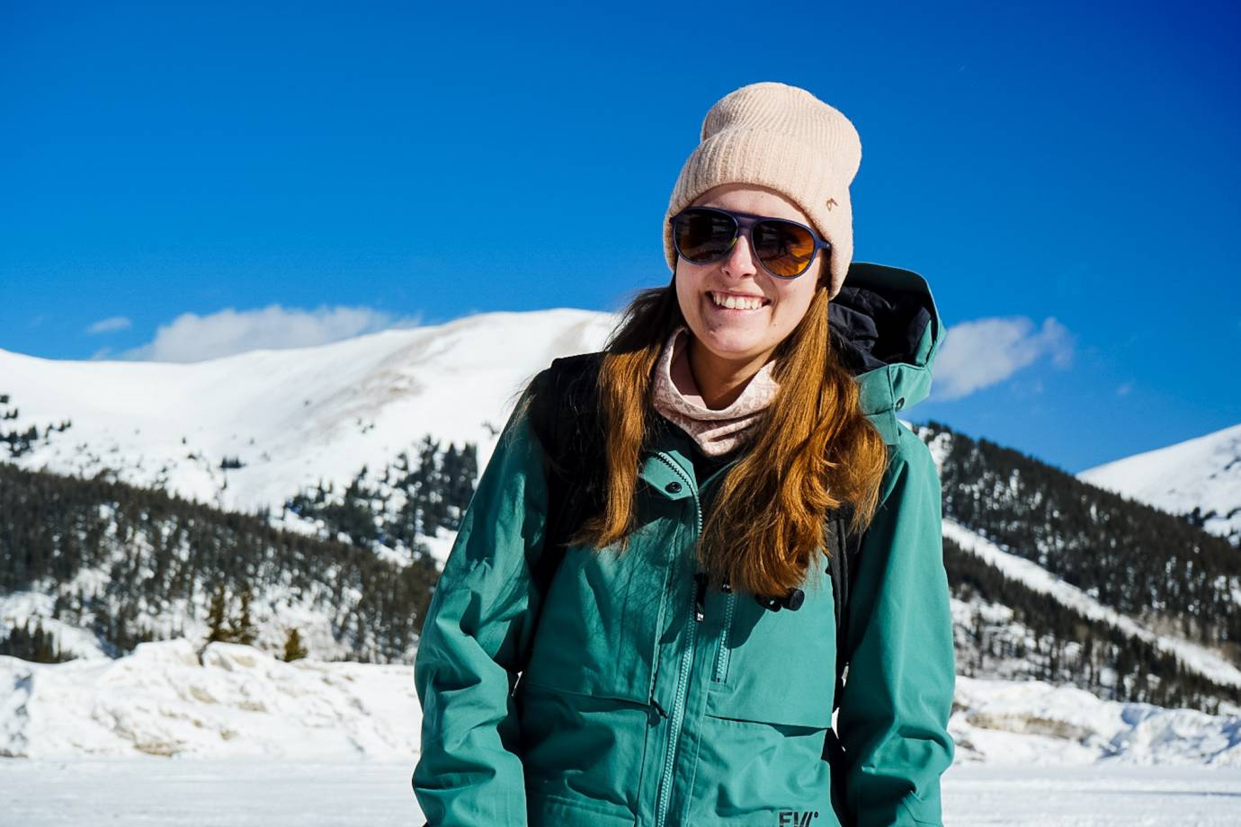 Editor Mary Murphy in the backcountry wearing an FW Ski Jacket, GORE-TEX bibs, pink hat and sunglasses