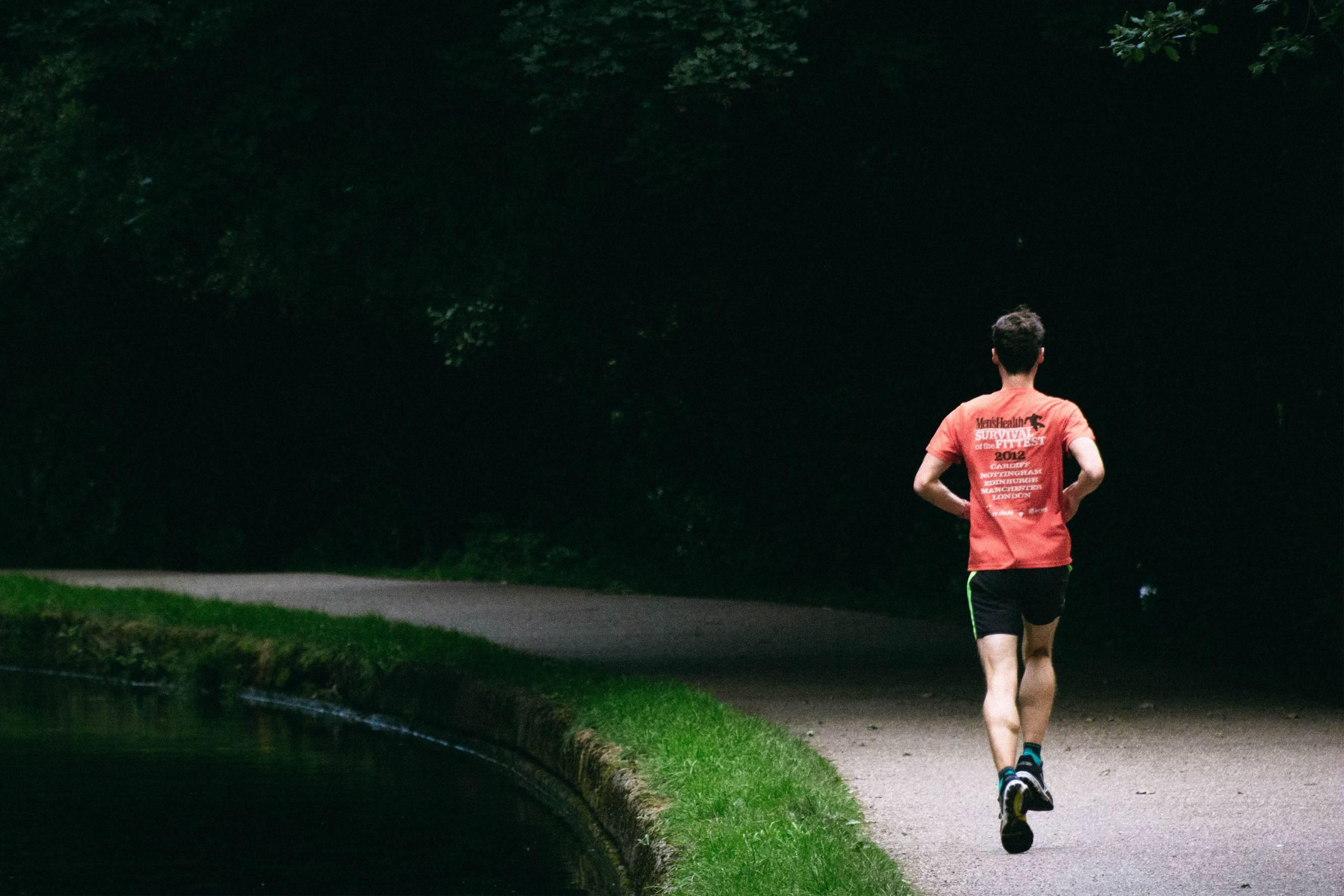 man running along gravel trail wearing red t-shirt