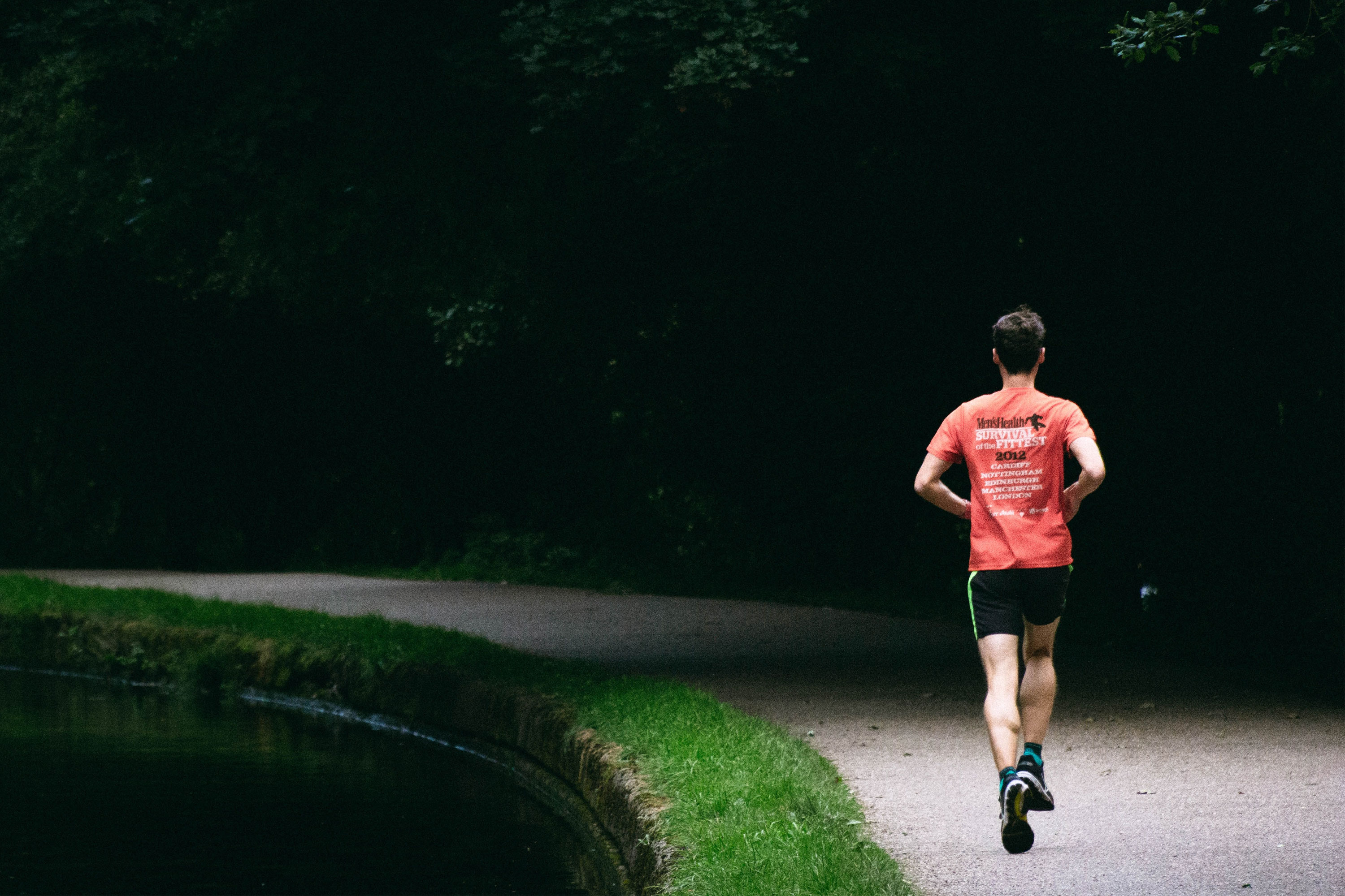 man running along gravel trail wearing red t-shirt