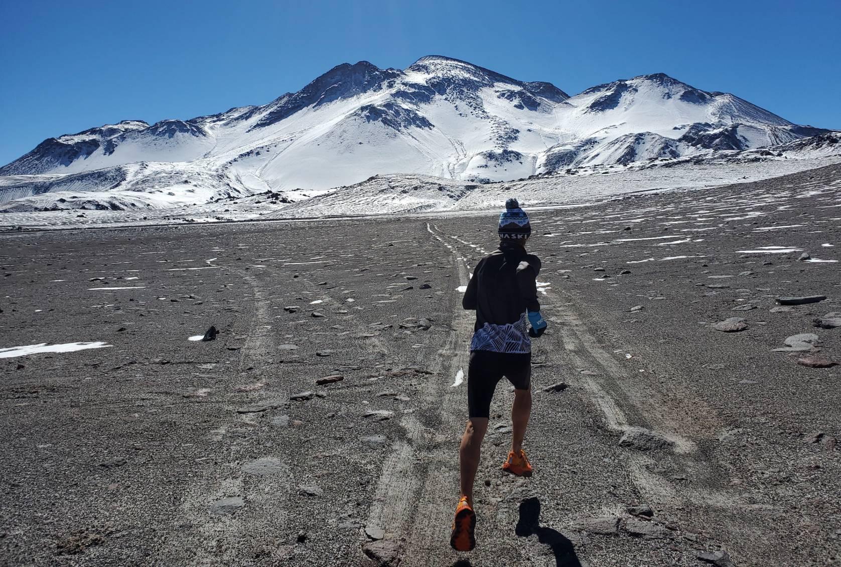 tyler andrews running towards mountain volcano