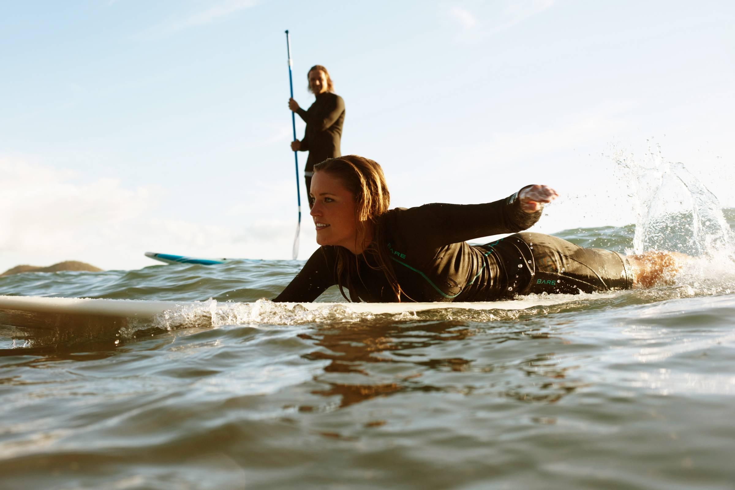 woman paddling on board, man on SUP