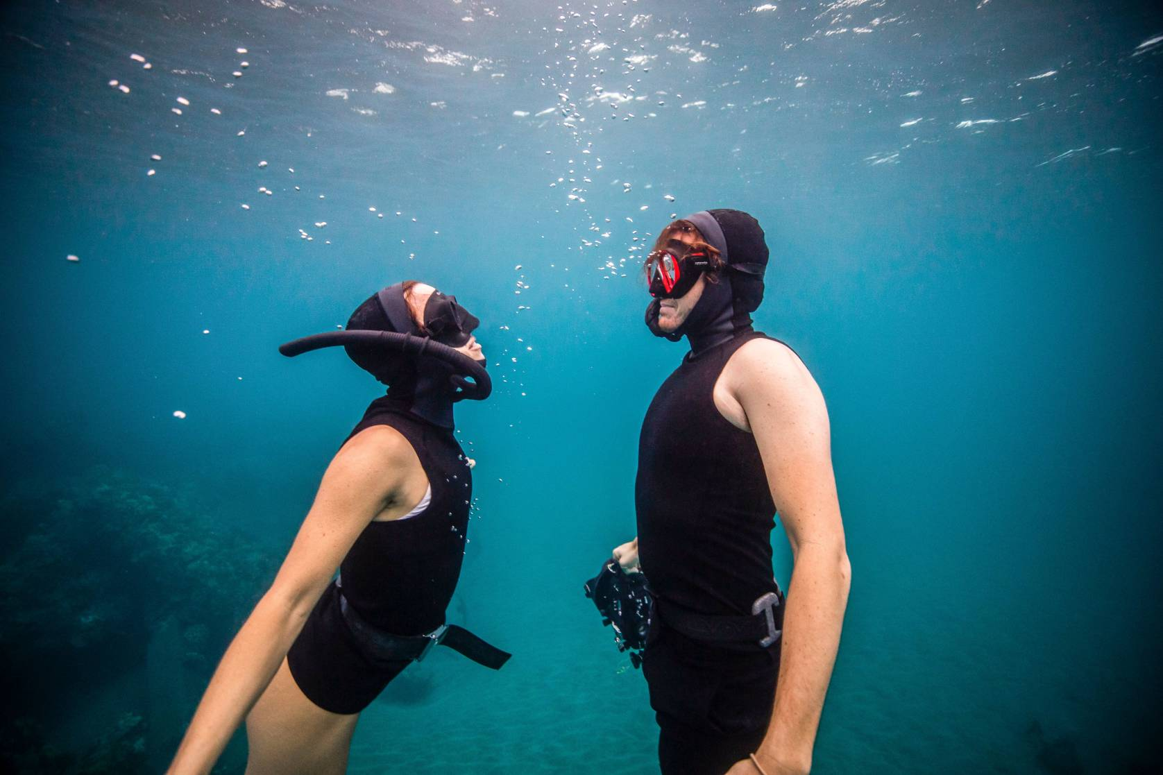 man and woman diving with Bare ExoWear Hooded Vest