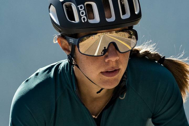 female cyclist in forest green jersey and black POC helmet