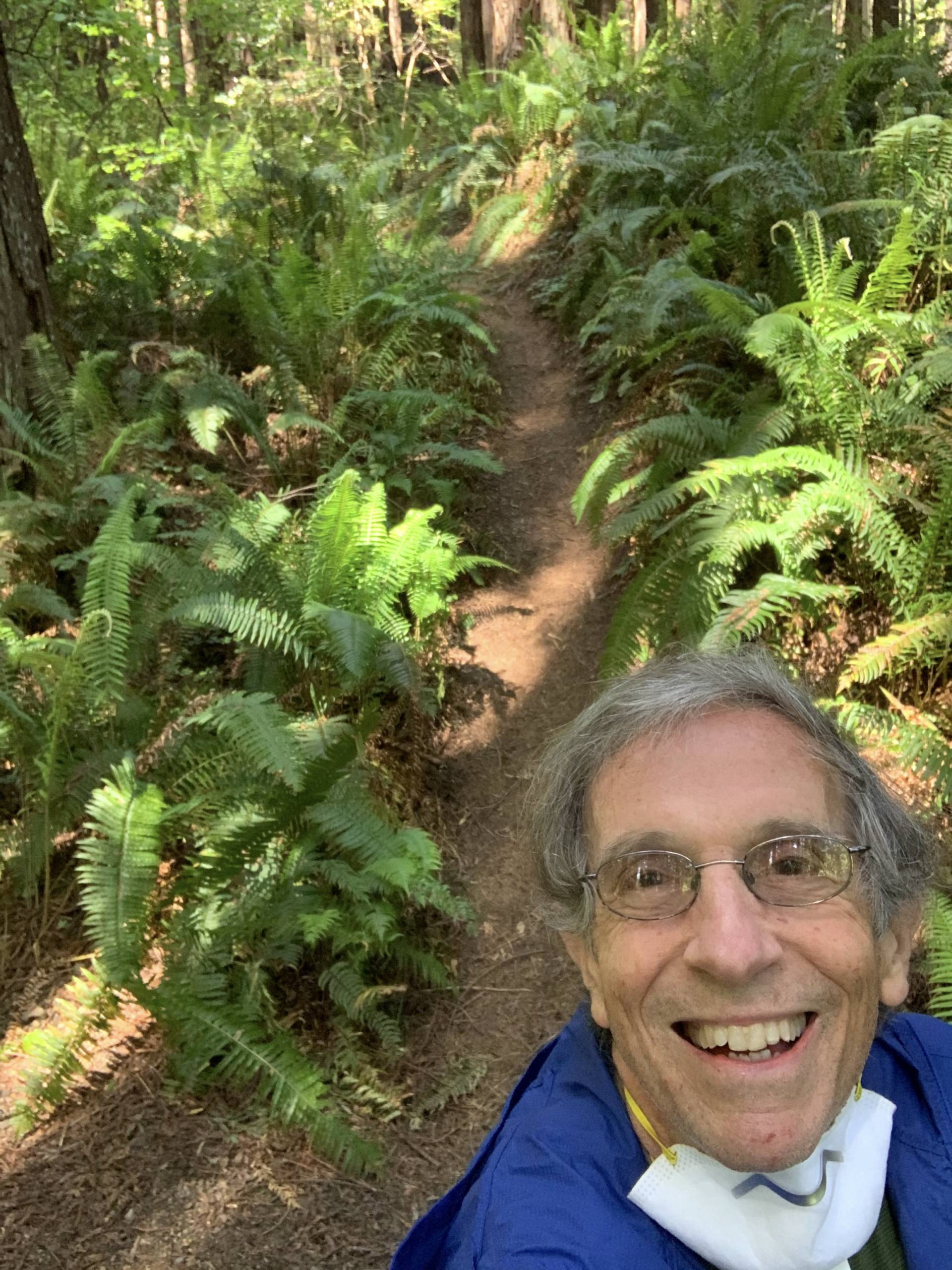 Eric Spector taking a selfie while running along a lush singletrack trail