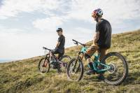 two mountain bikers stopping on the crest of the path