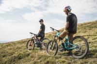 two mountain bikers pausing along ridge of trail