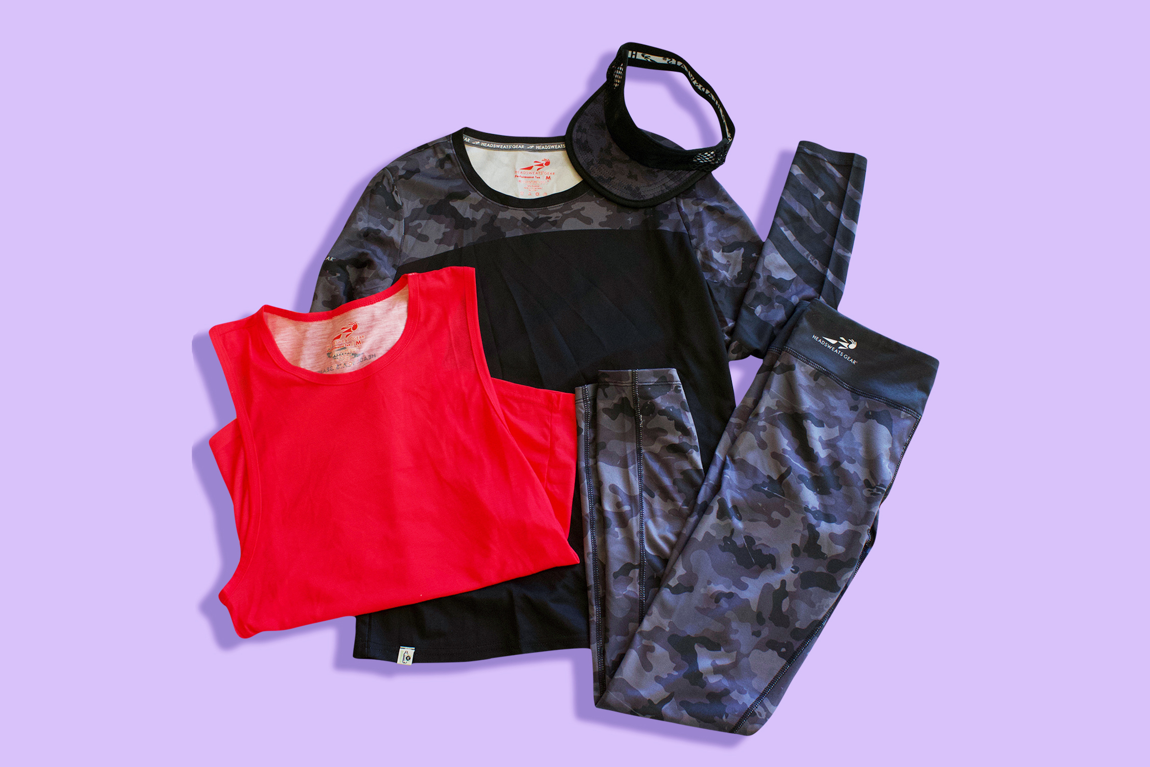 Headsweats Active Line pieces in Dark Camo and pink folded on flat surface against purple background