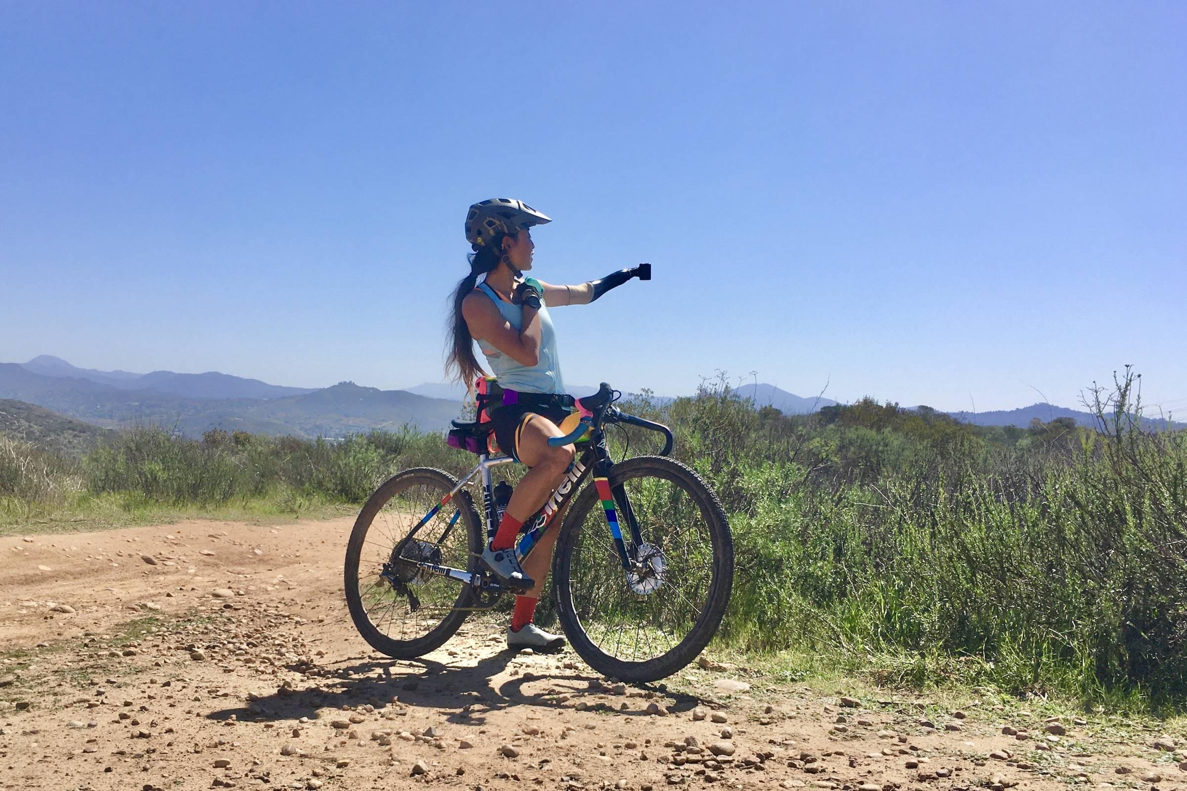 Josie Fouts straddling her bike, pointing towards route on horizon