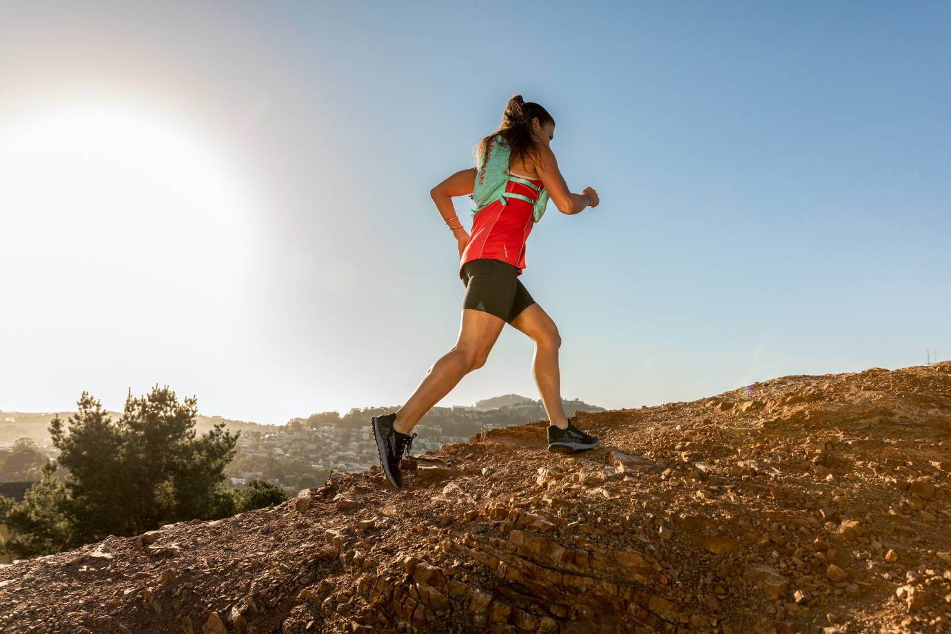 female trail runner moving uphill wearing Nathan apparel and pack
