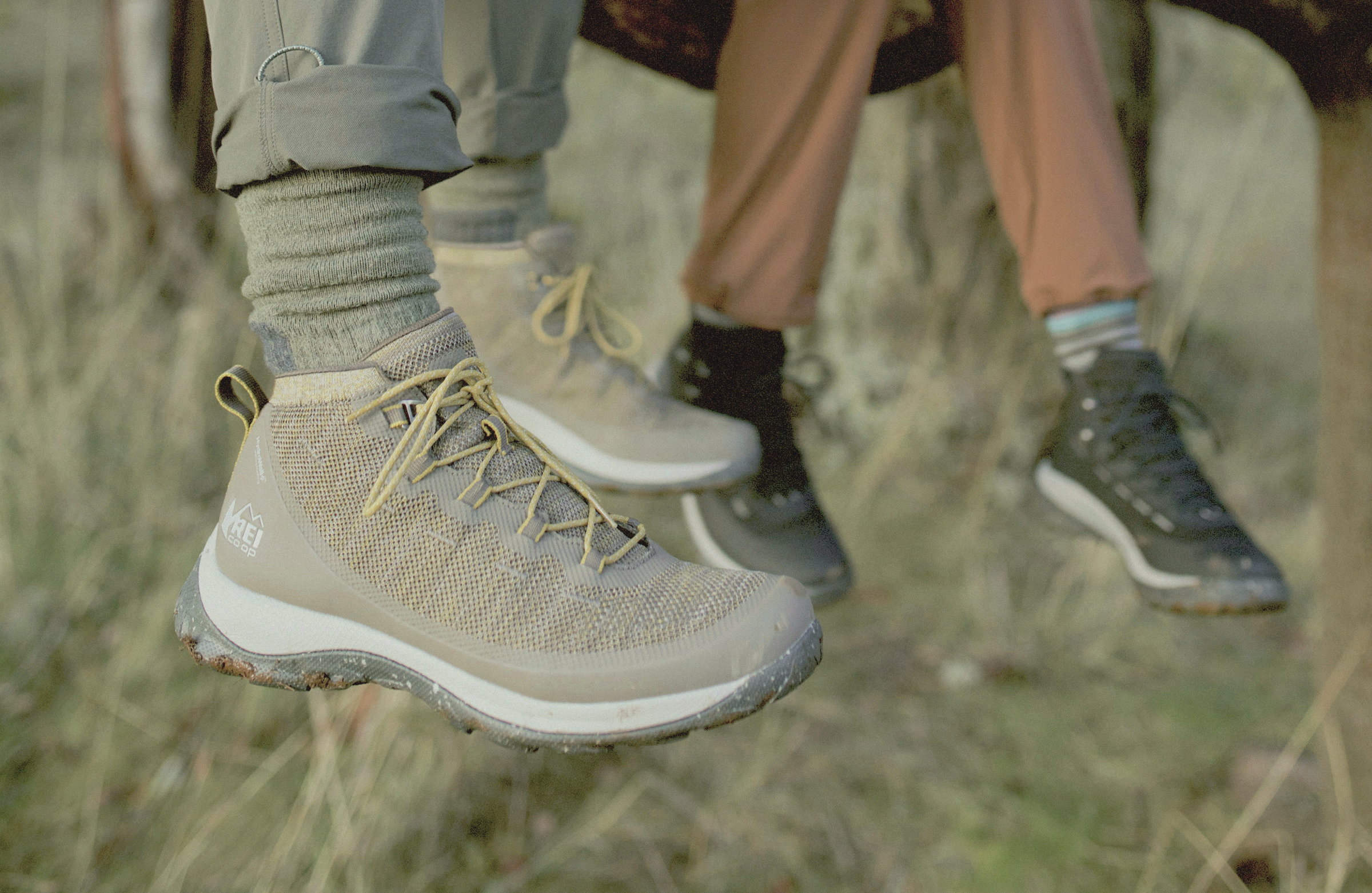 REI Flash hiking boot on feet with grass in background