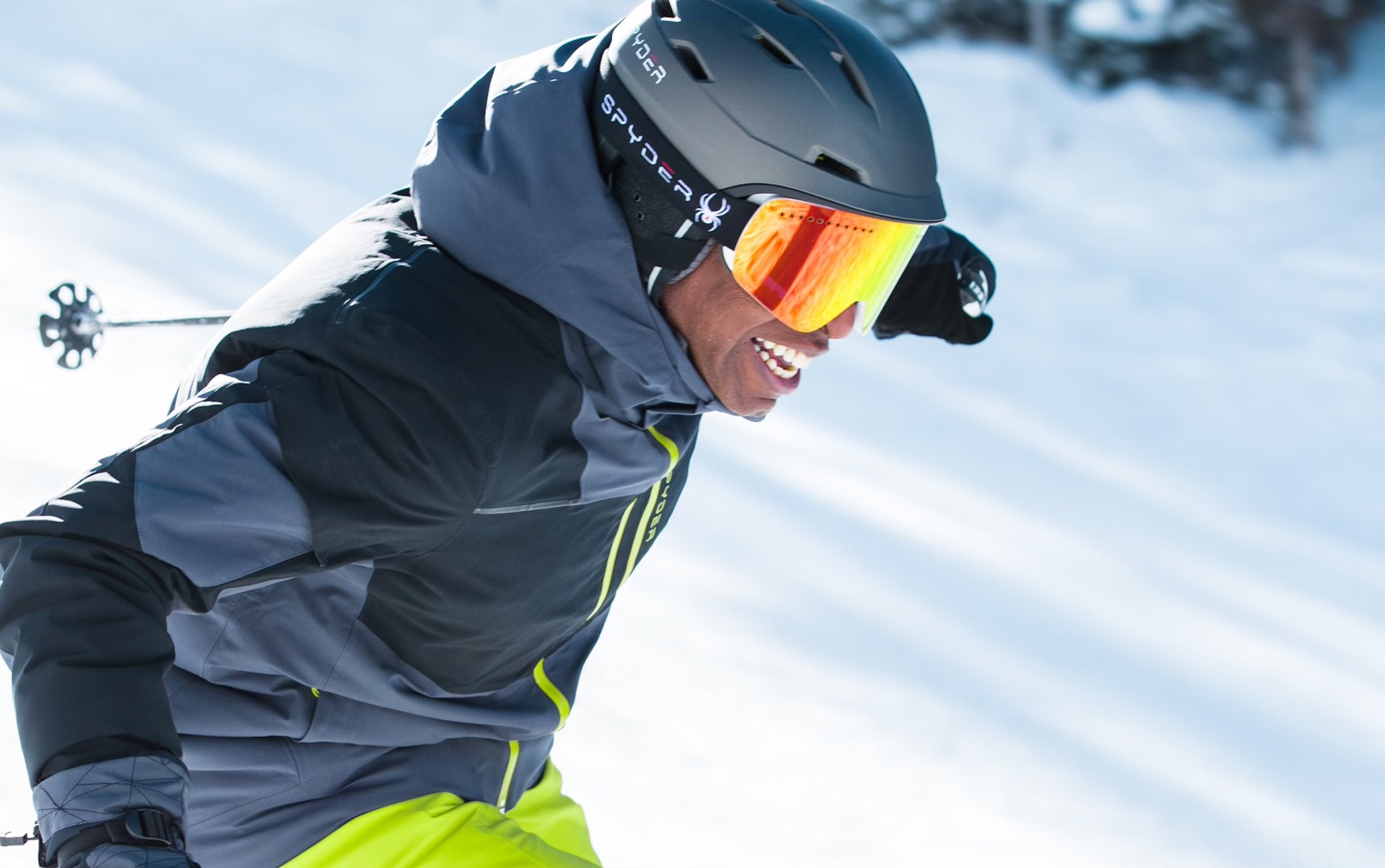 Black man wearing SPYDER goggles while downhill skiing and smiling