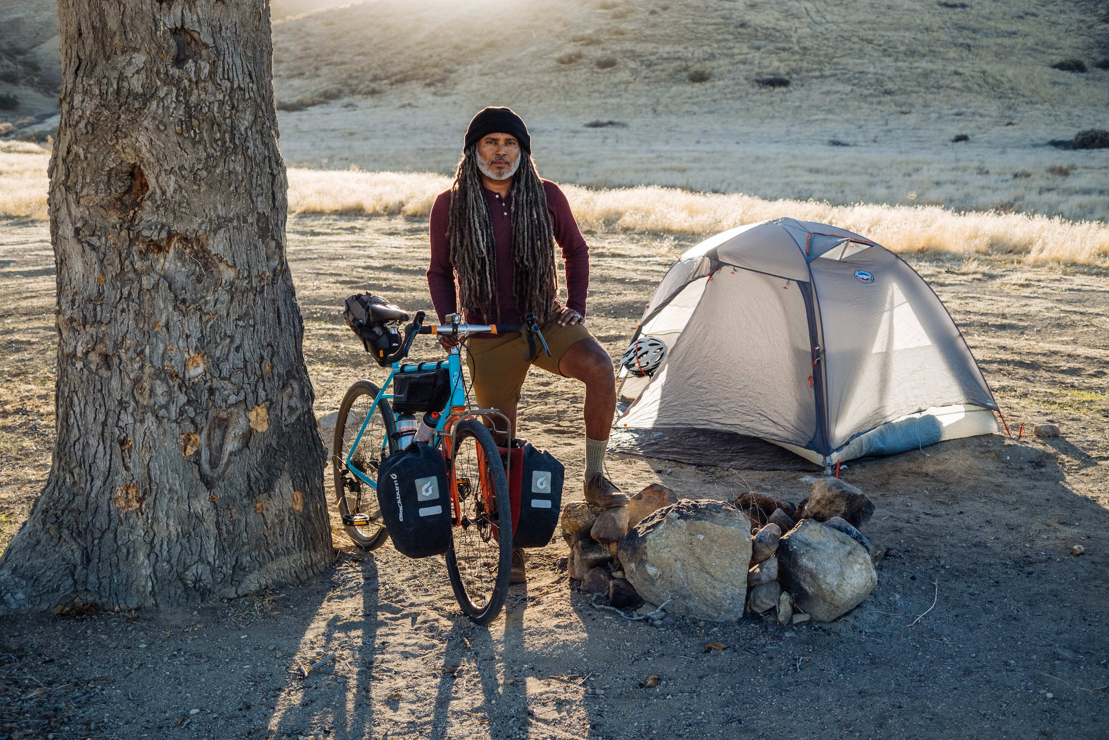 Bicycle Nomad Erick Cedeño standing next to small tent and tree with his bike