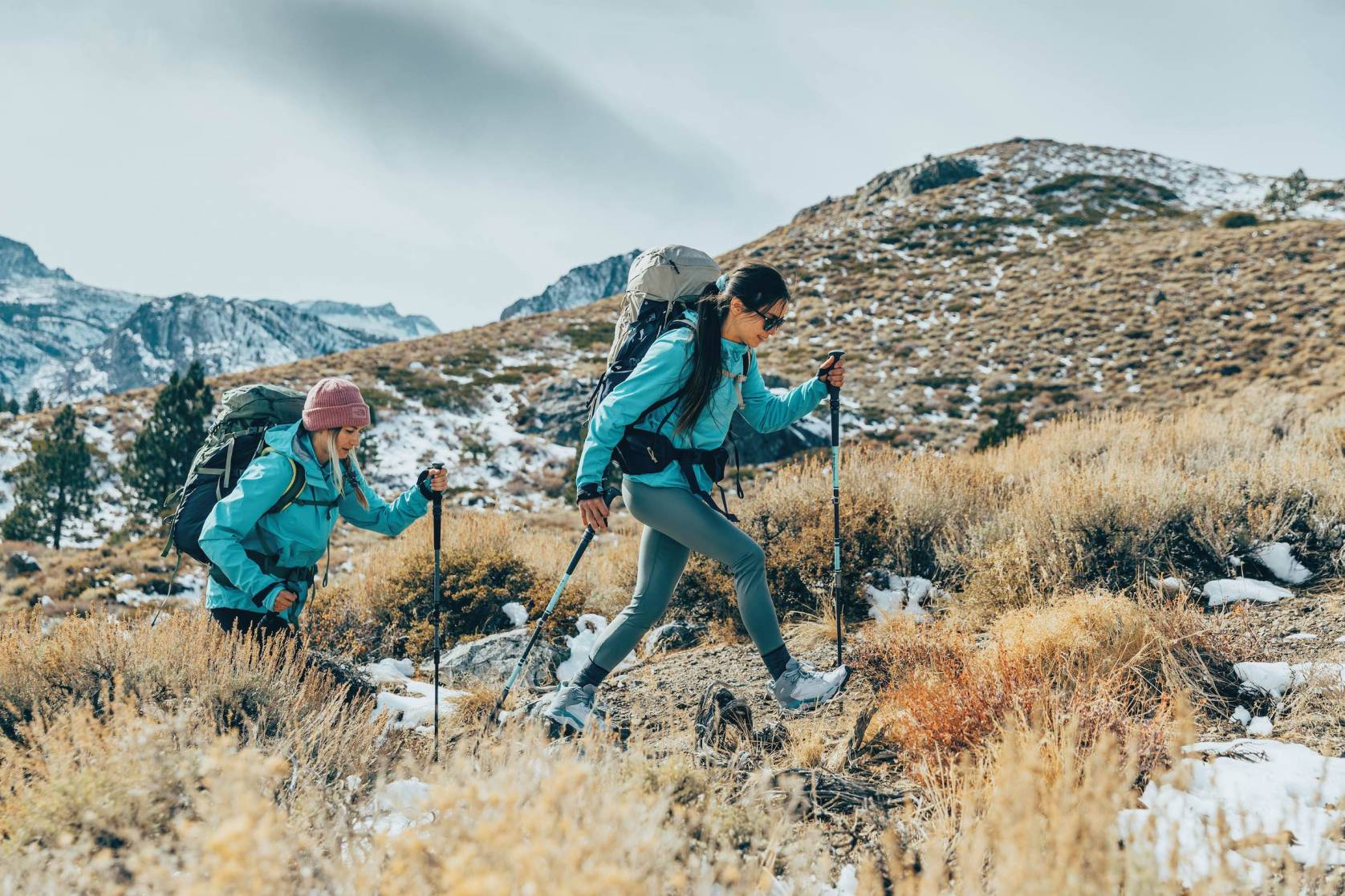 Two female hikers in matching jackets hiking uphill in winter