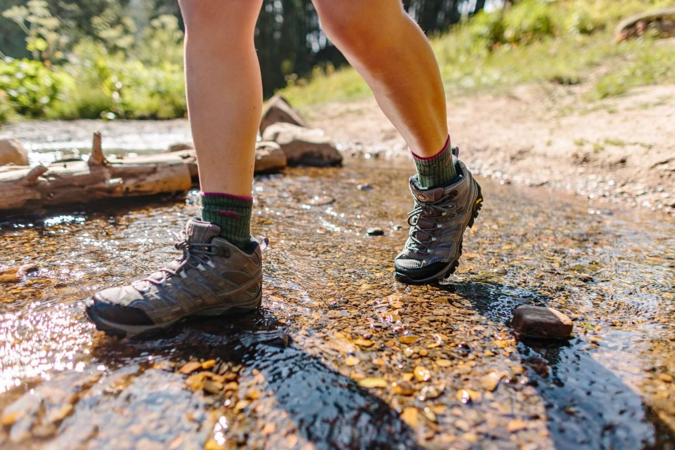 hiker wearing hiking boots through stream