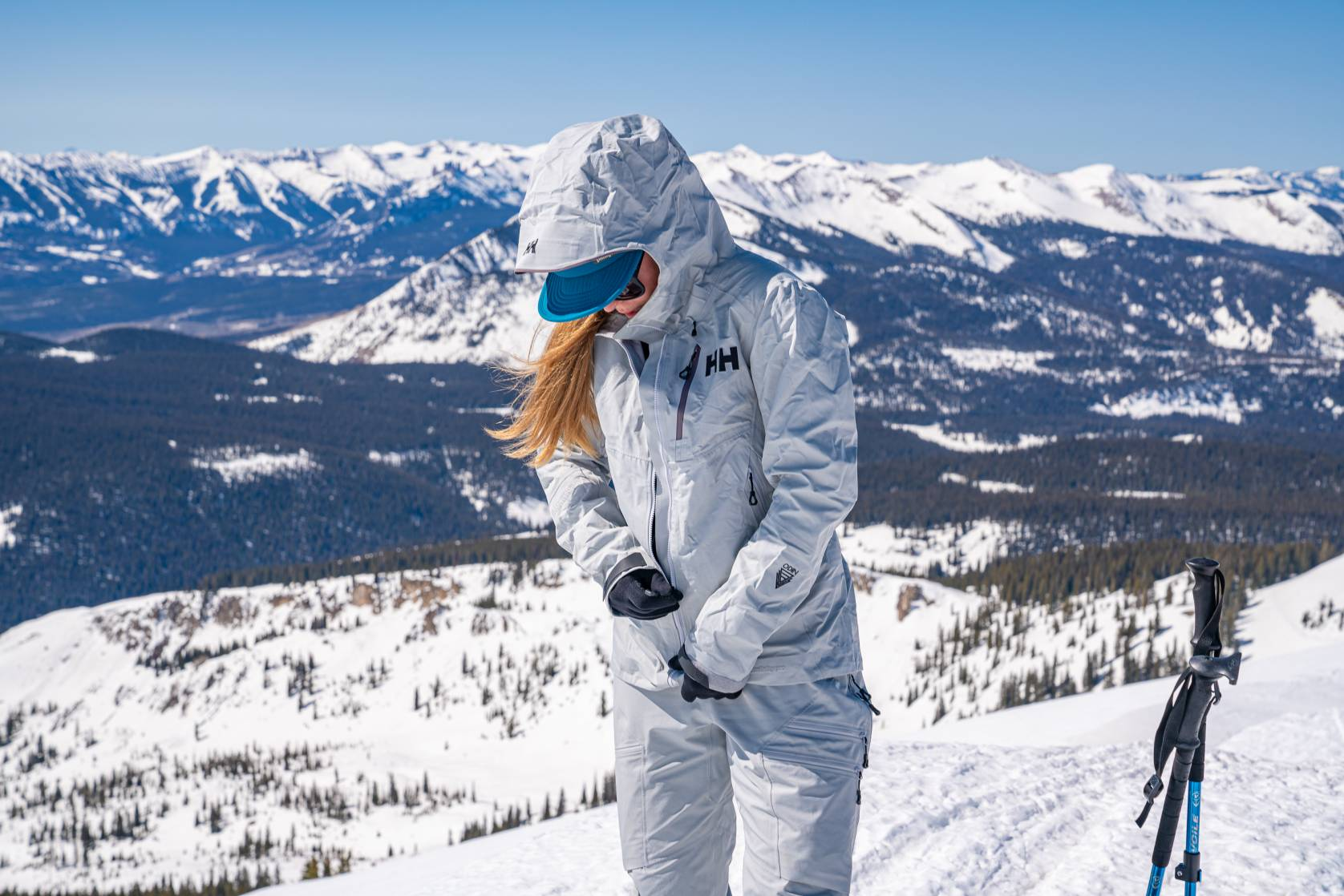 Female zipping up the Helly Hansen white Pro Shell, wearing a hat and hood