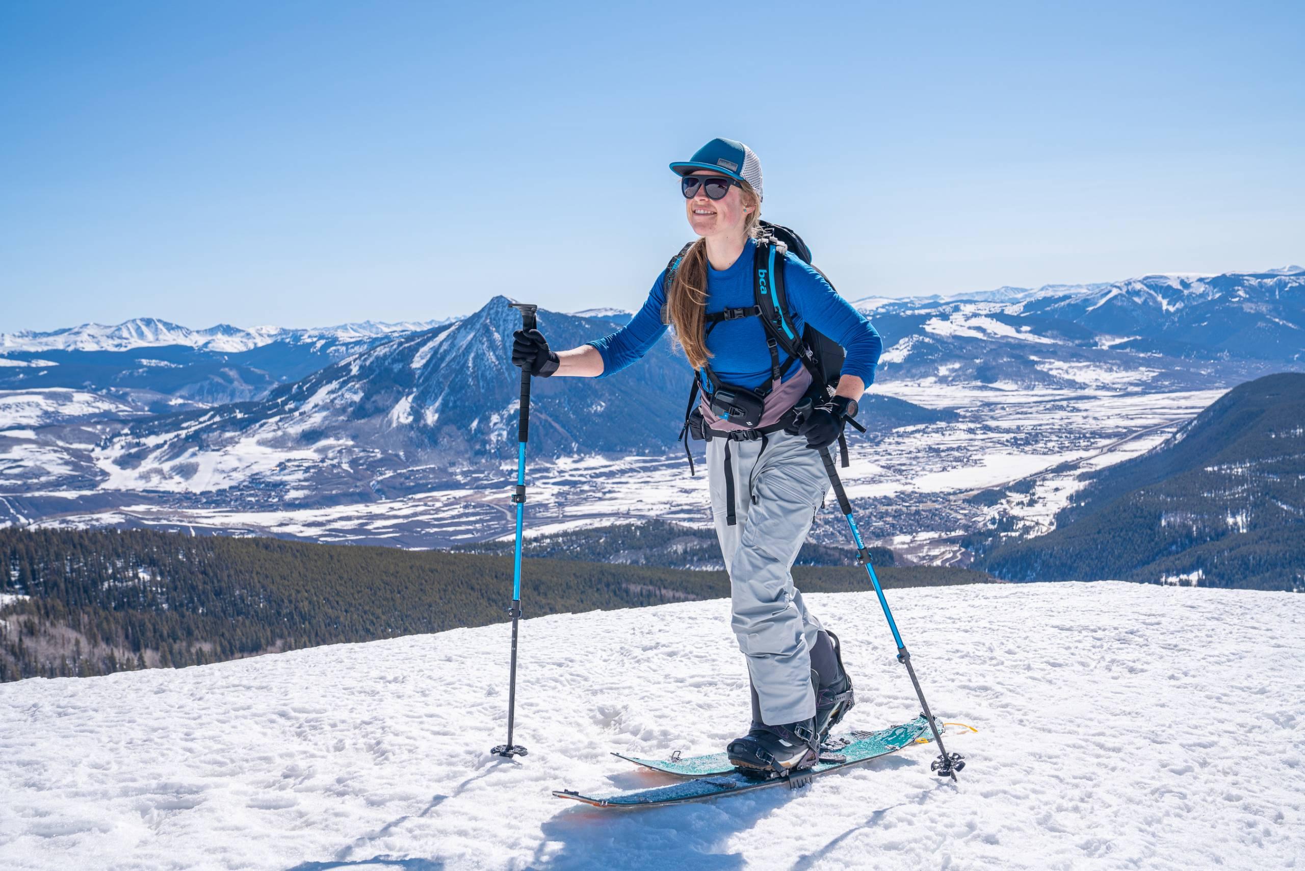 Weibliche Splitboarderin, die sich in Helly Hansen LifaLoft Pro Shell Lätzchen an einem sonnigen Tag in den Bergen bergauf bewegt