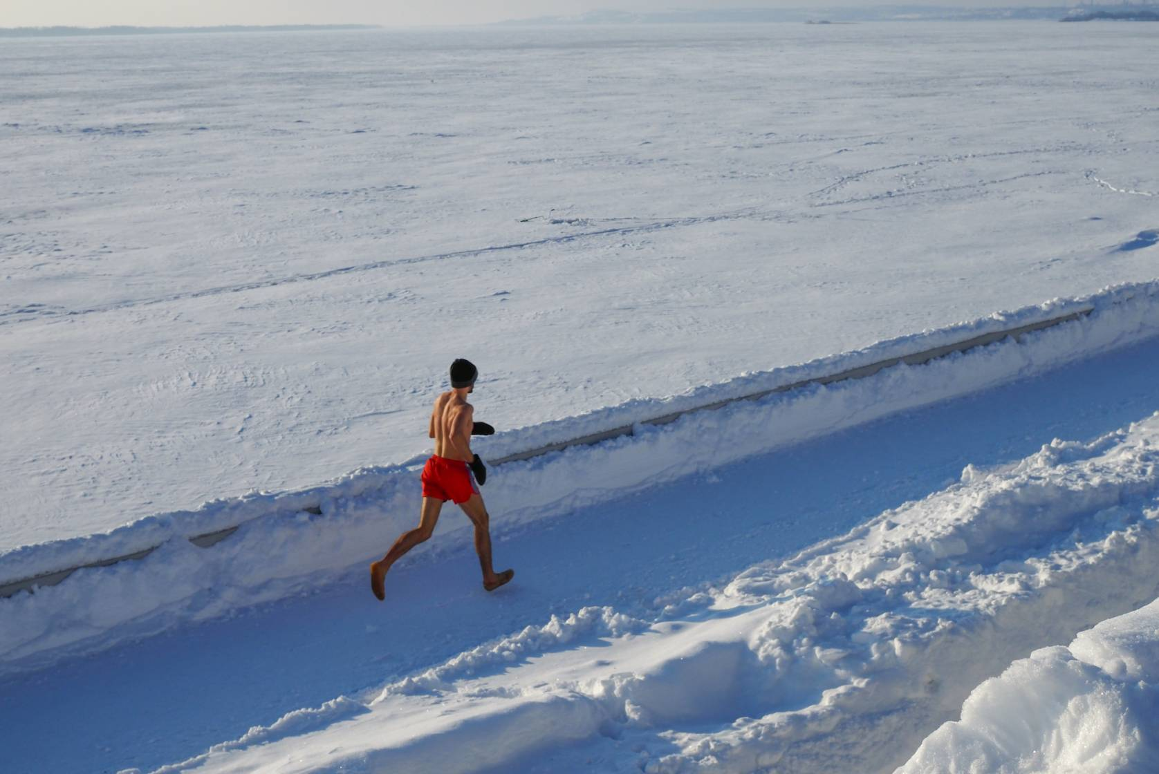 man running in red shorts barefoot down lane of snow