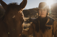 gillian larson in cowboy hat standing next to her horse on a trail