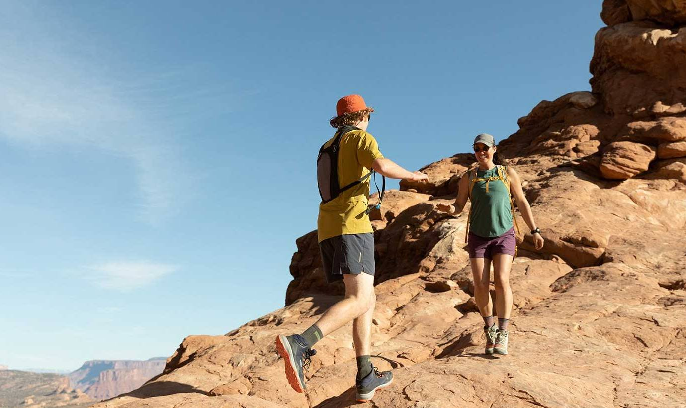 two hikers in short sleeves and keen boots hiking over rocky terrain