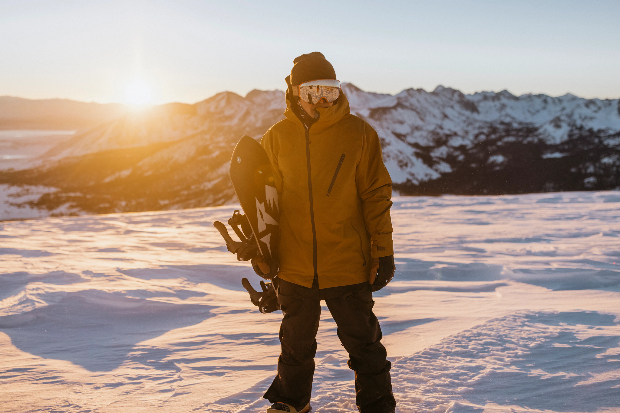 Snowboarder lonnie kauk standing on flat snow holding board