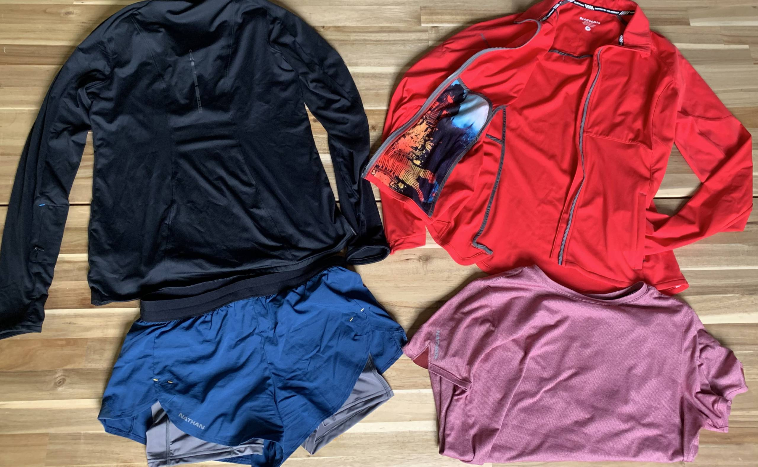 clockwise: a long sleeve, a jacket, and tee, and a pair of shorts laid out on table