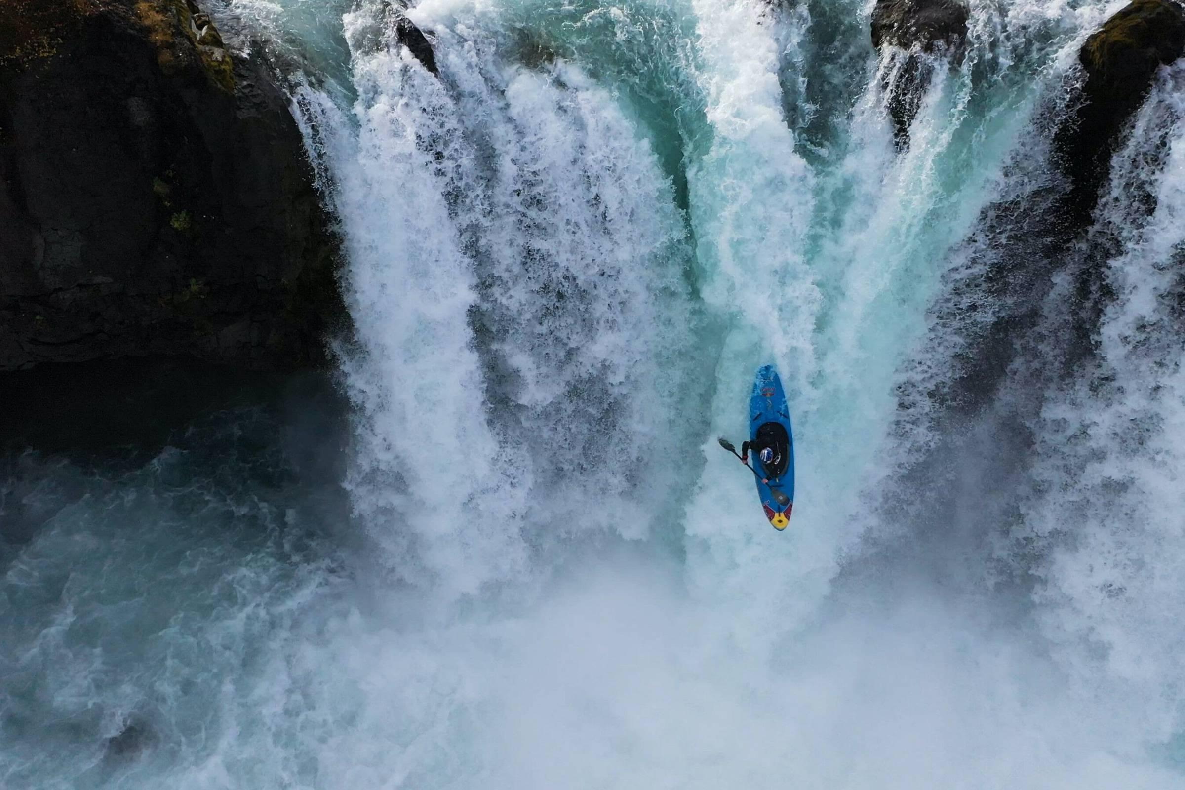 Nouria Nouman in blue kayak going down massive waterfall