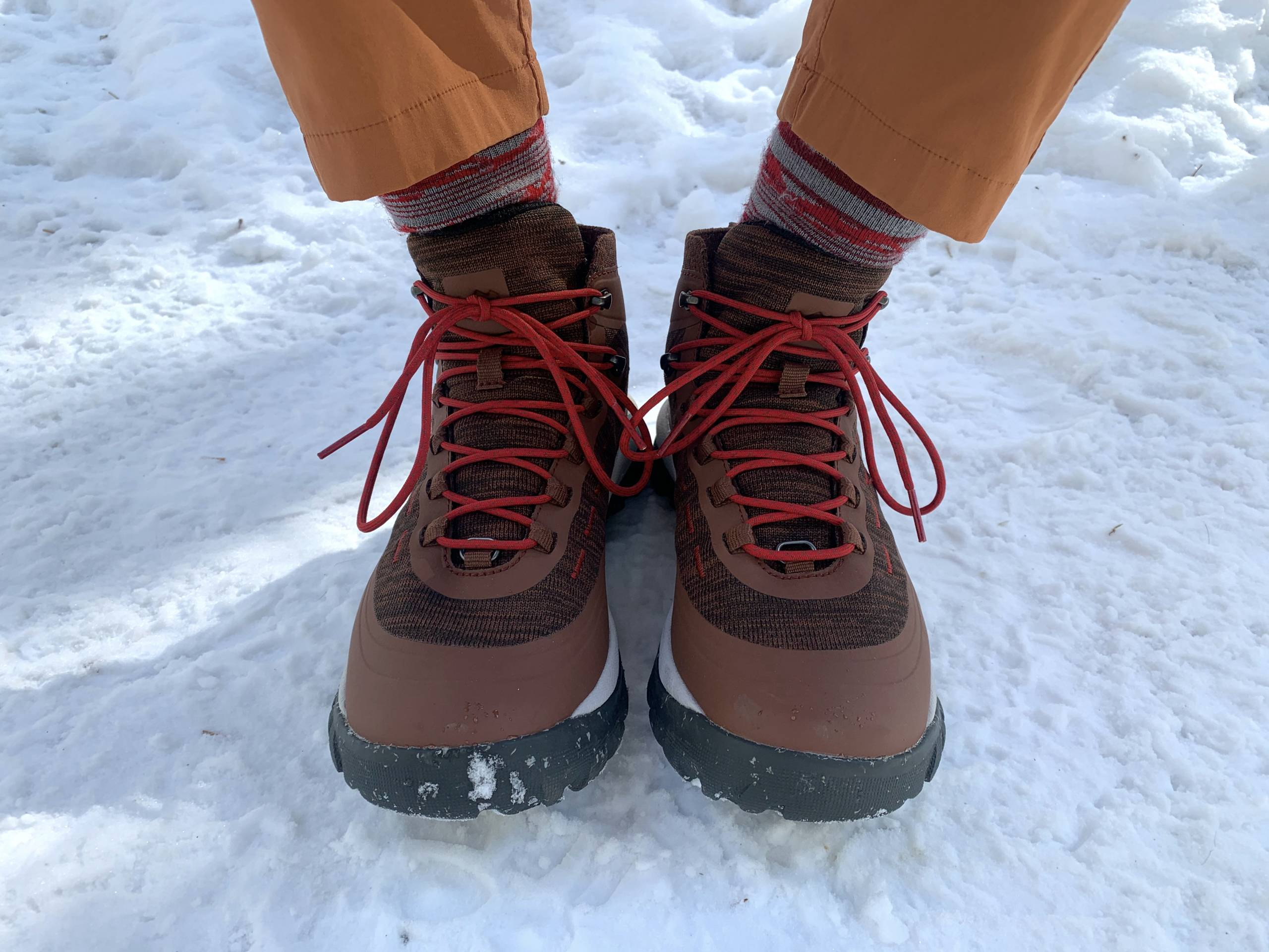 Author wearing pair of brown REI Traverse boots in snow, shown from ankles down