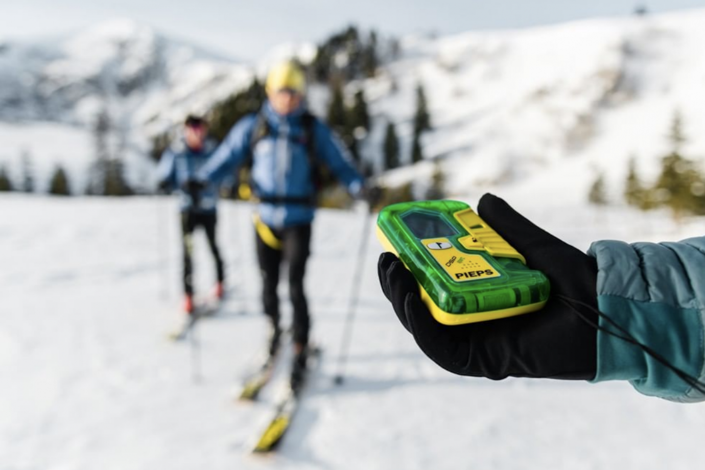 skier holding up pieps dsp pro transceiver with two other skiers in background