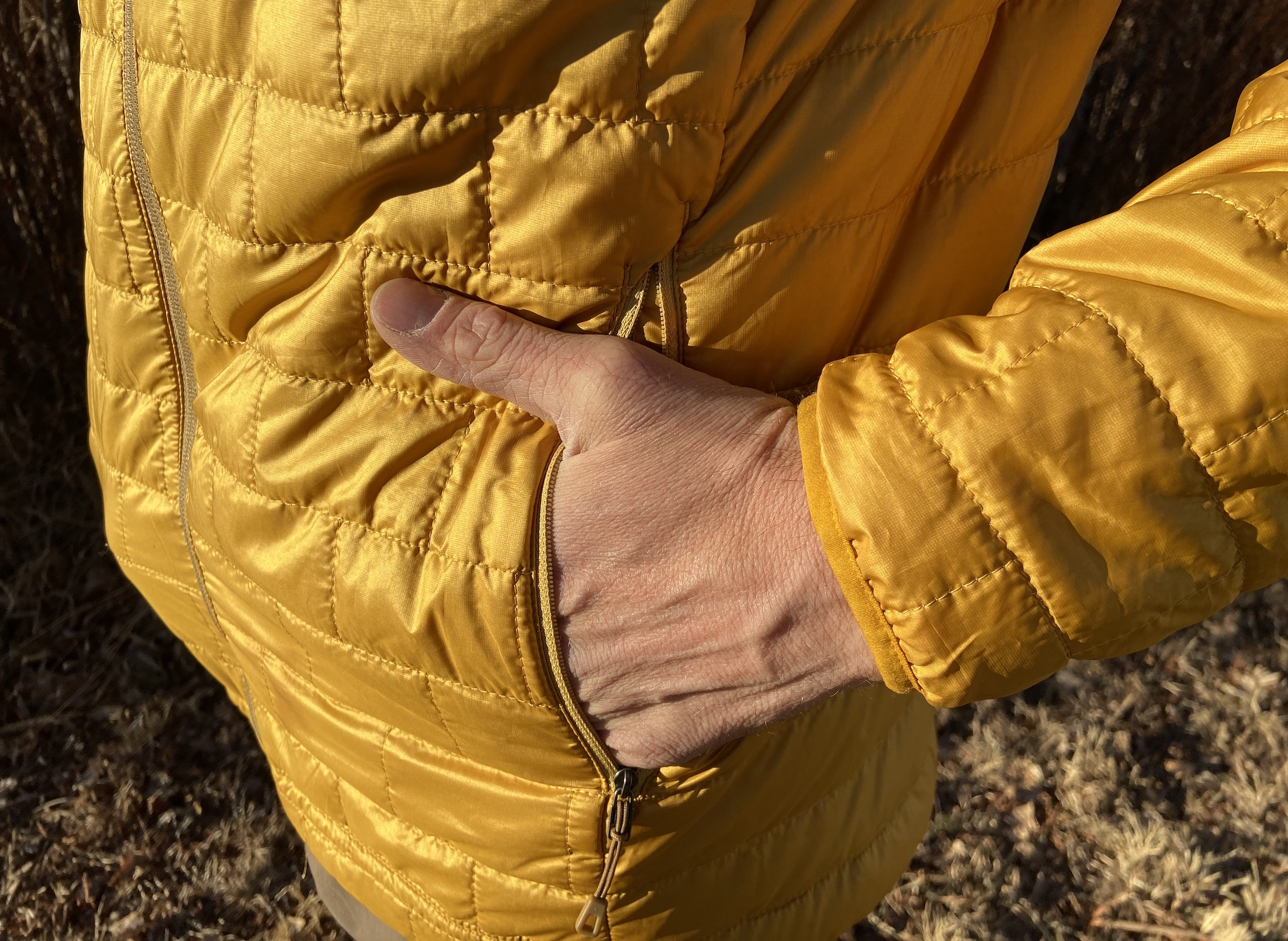 close up of man's hand in pocket of the Patagonia nano puff jacket in gold