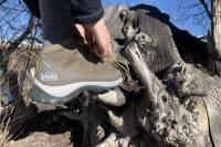 Autor atando zapatos REI Flash con brazaletes largos negros