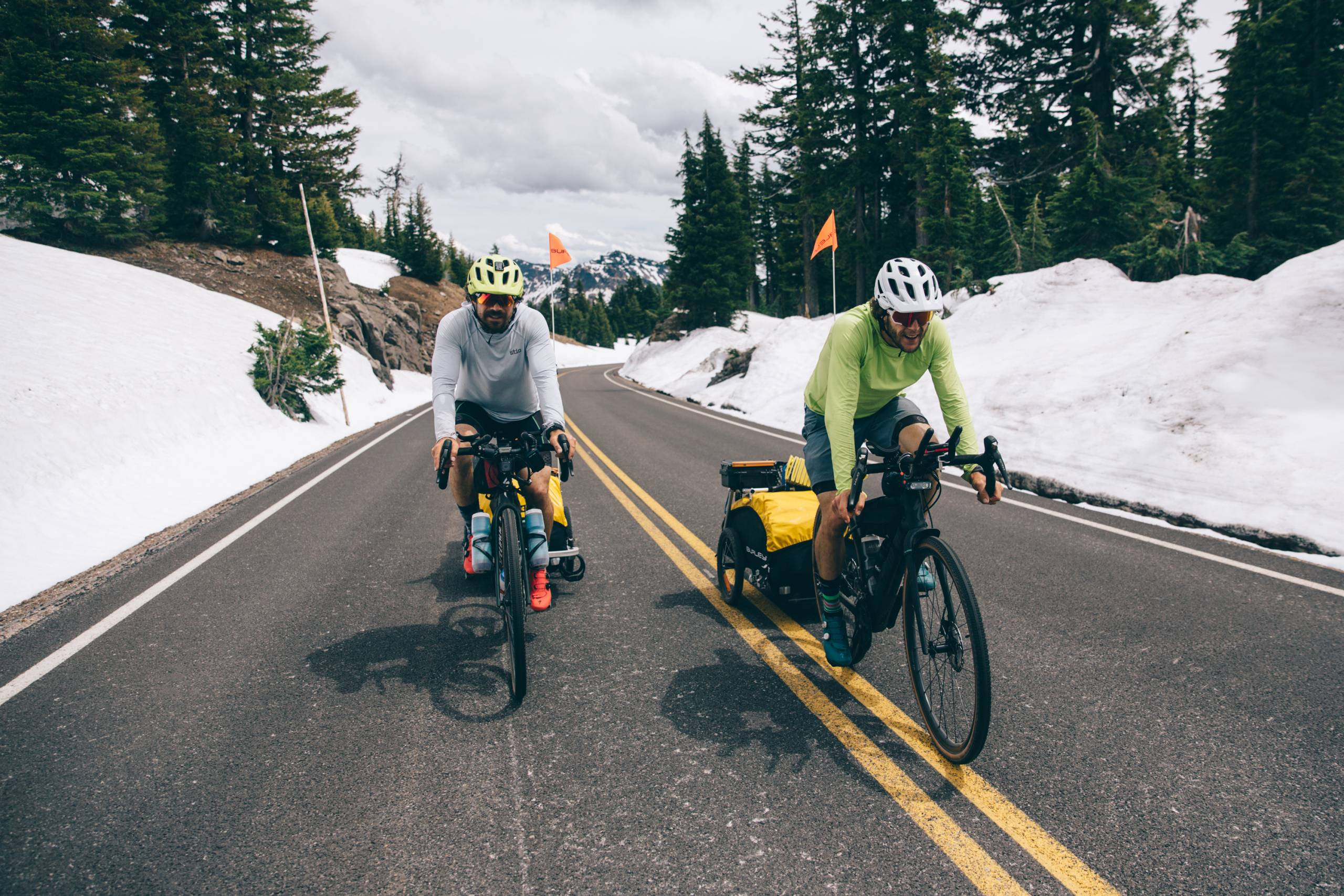two guys on bikes with trailers pedaling on road lined with snow