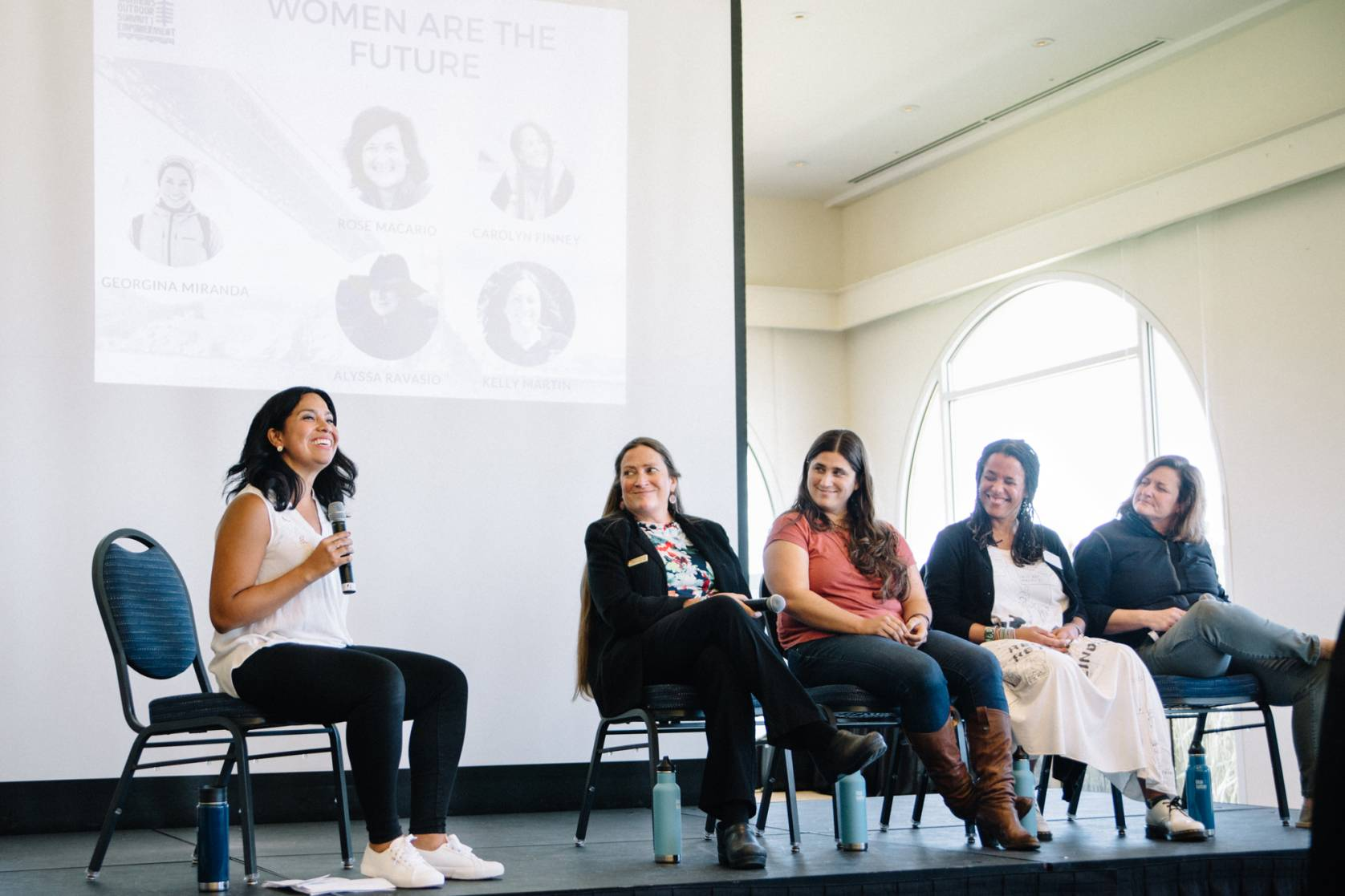 5 women, one holding a microphone, on a speaking panel at a Women's Outdoor Summit