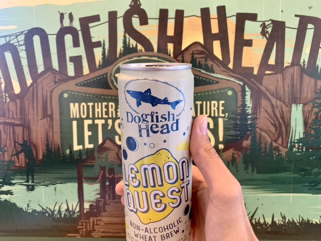 A can of Dogfish Head lemon quest with a Mother Nature and dogfish head poster in the background