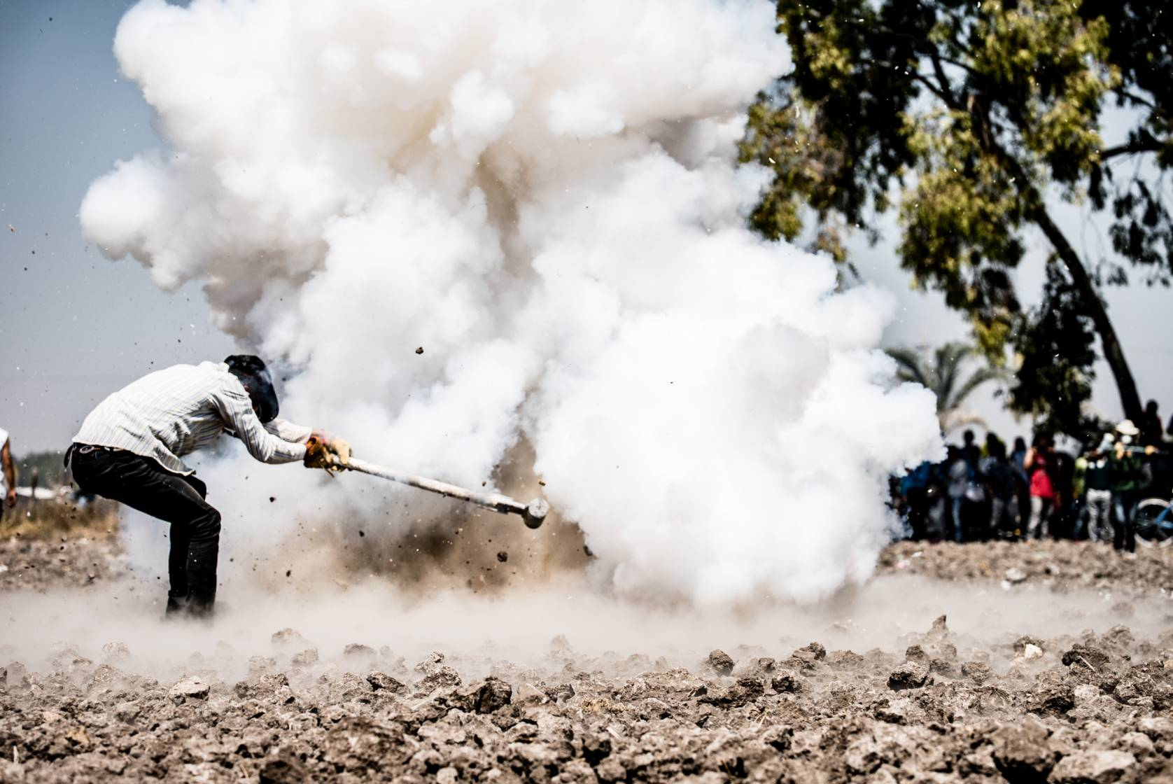 man with a giant hammer and dust cloud explosion