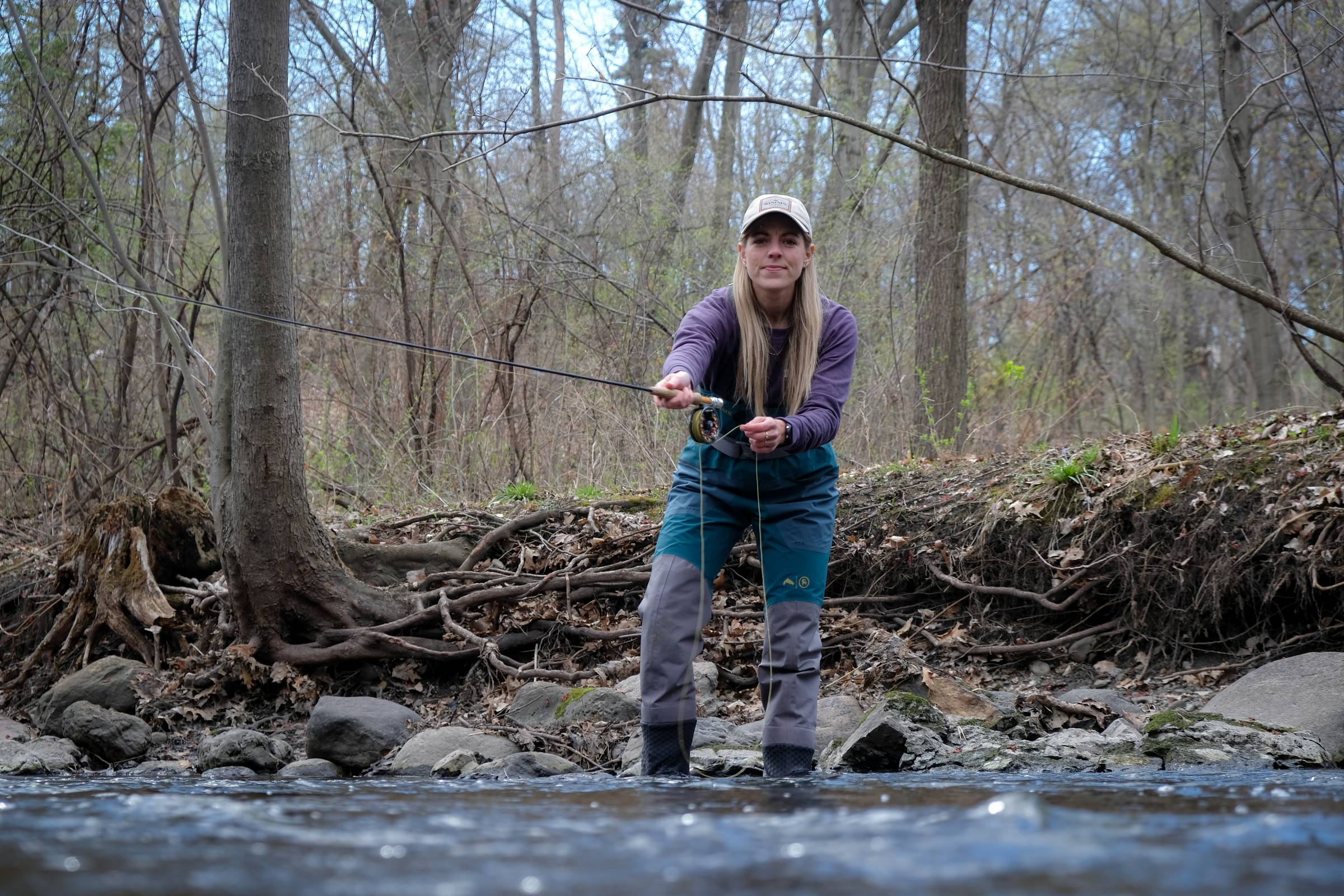 Person casting a fly fishing rod in Simms Backcountry flyweight fly fishing waders lifestyle