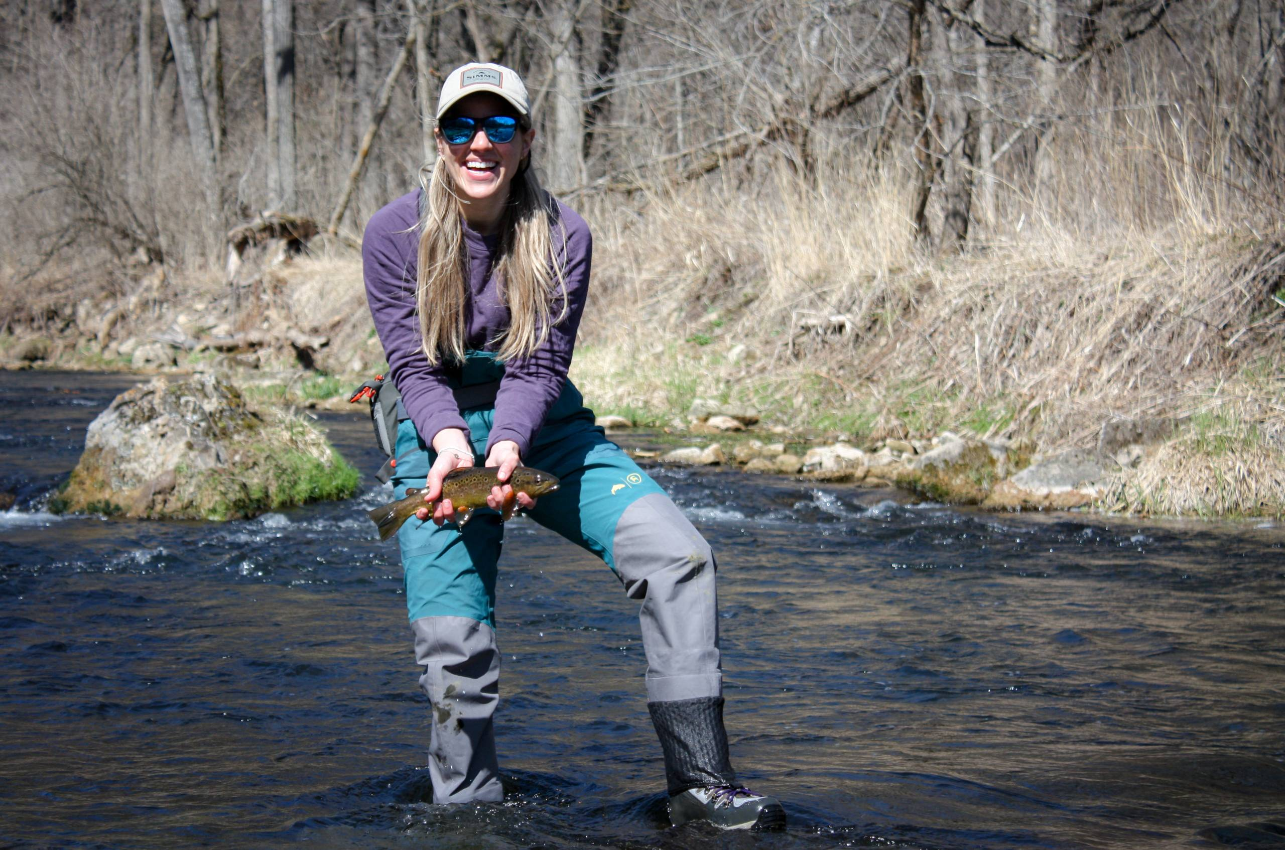 Person holding trout in Simms Backcountry flyweight fly fishing waders lifestyle