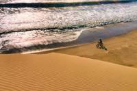 Kate Lemming cycling across a Namibia desert beach