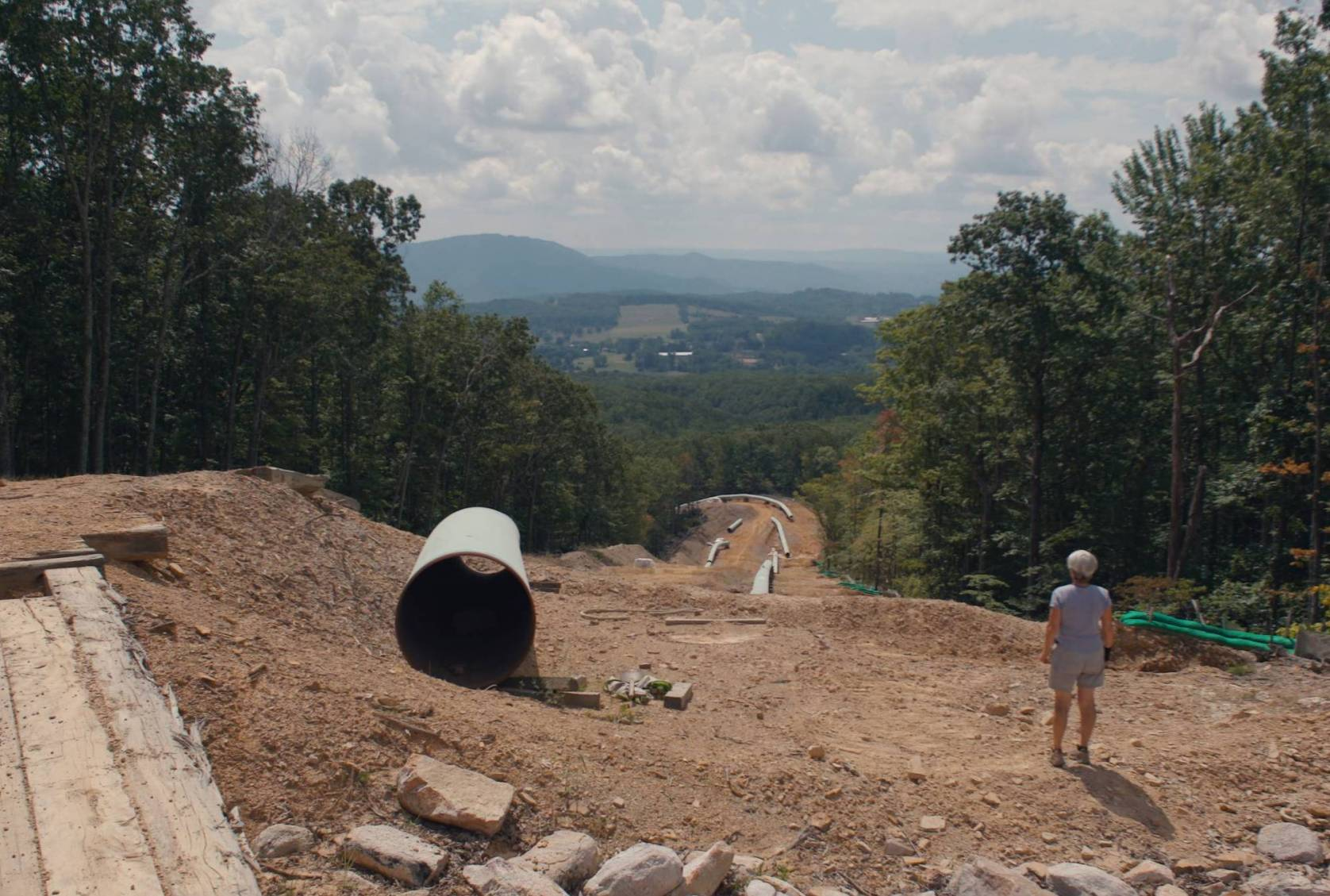 a person looking down a steep hill cluttered with segments of a pipeline