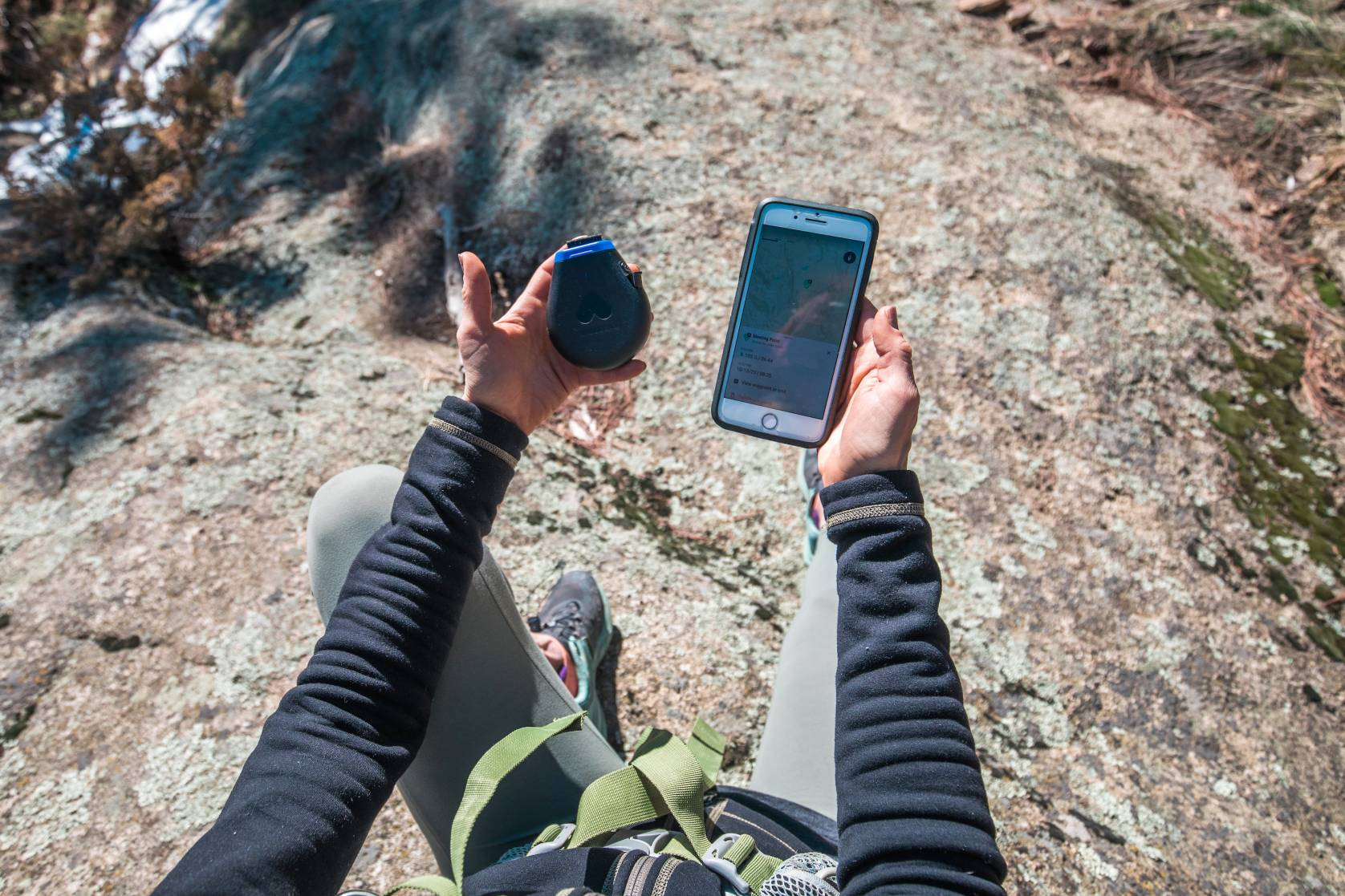 hiker holding a Somewear hotspot and smartphone while sitting on a rock