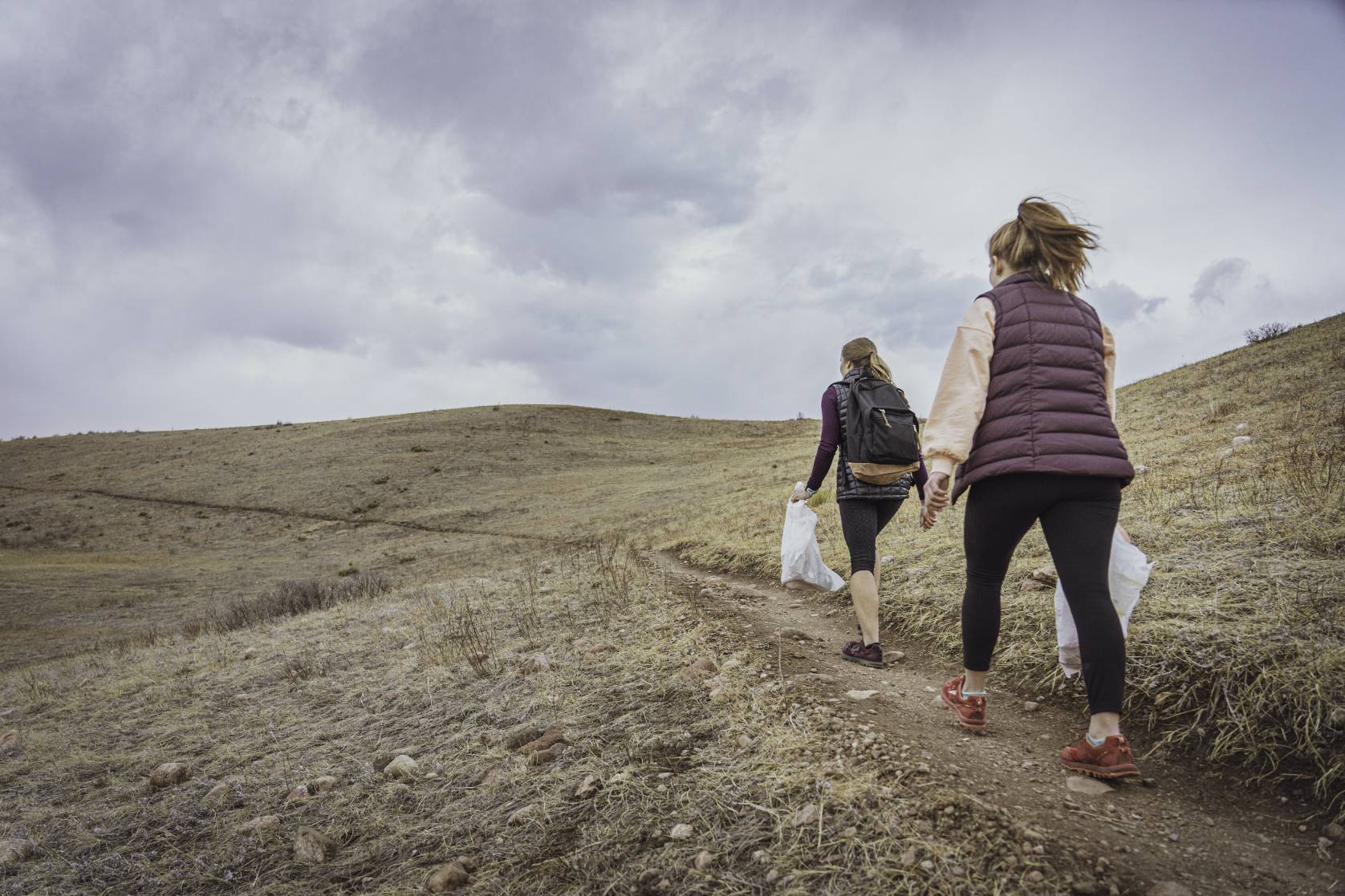two female hikers with trash bags walking uphill