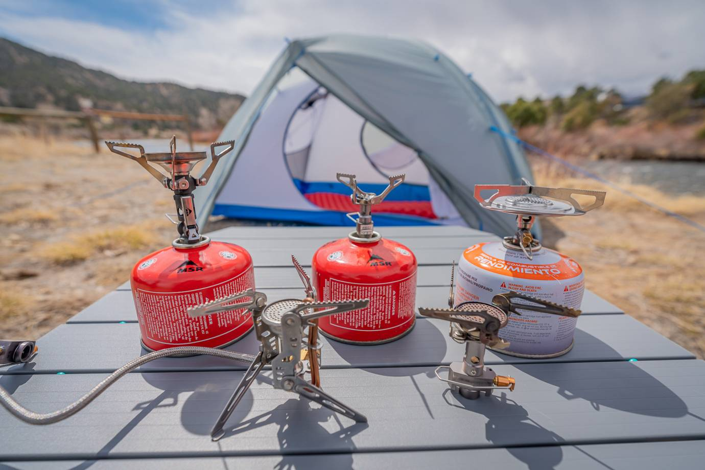 five different lightweight backpacking stoves with fuel canisters and a tent in the background